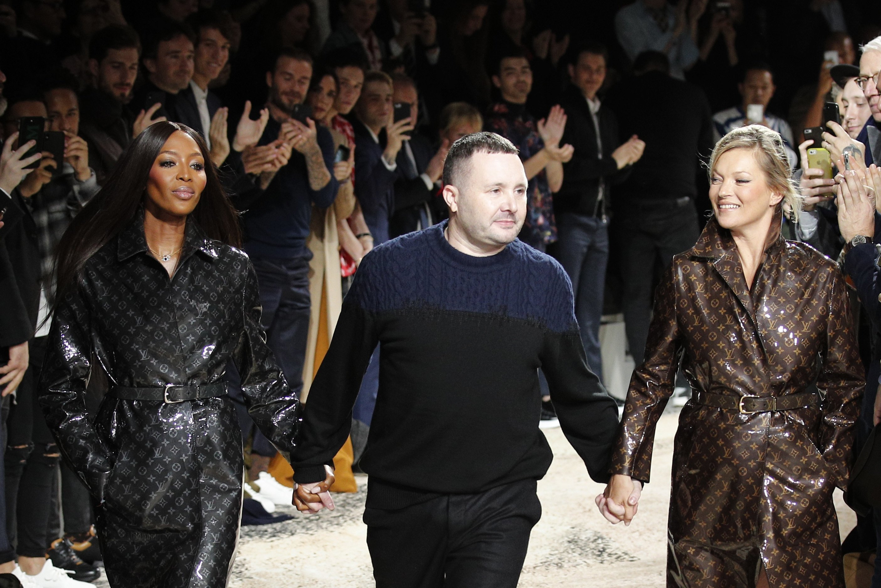 Designer Kim Jones (C) accepts applause as he walks with models Kate Moss (R) and Naomi Campbell (L) after his Louis Vuitton Men's Fall-Winter 2018-2019 fashion collection was presented in Paris, France, Jan.18, 2018. (AP Photo)