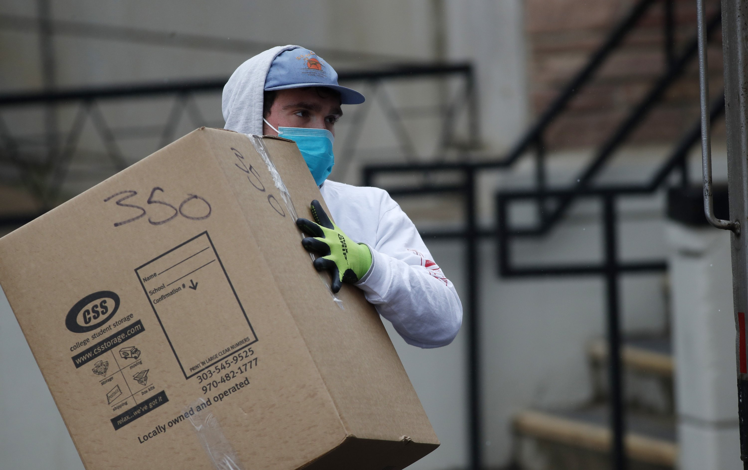 A worker wearing gloves and a surgical mask loads a box into a van while cleaning out dormitory rooms on the campus of the University of Colorado, April 2, 2020, in Boulder, Colo. (AP Photo)