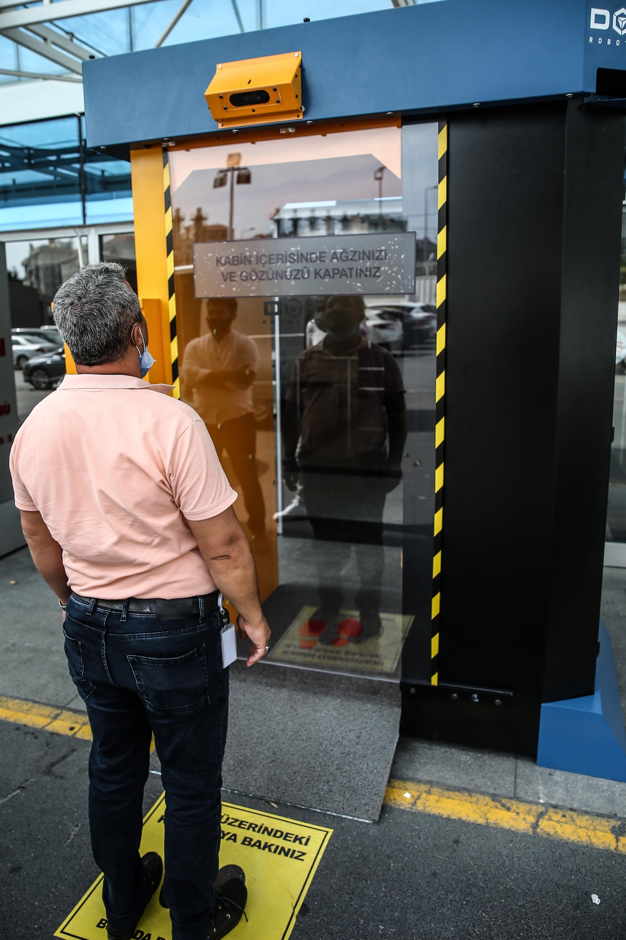 A man is seen in front of a smart disinfection and sanitation cabin developed by DOF Robotics. (AA Photo)