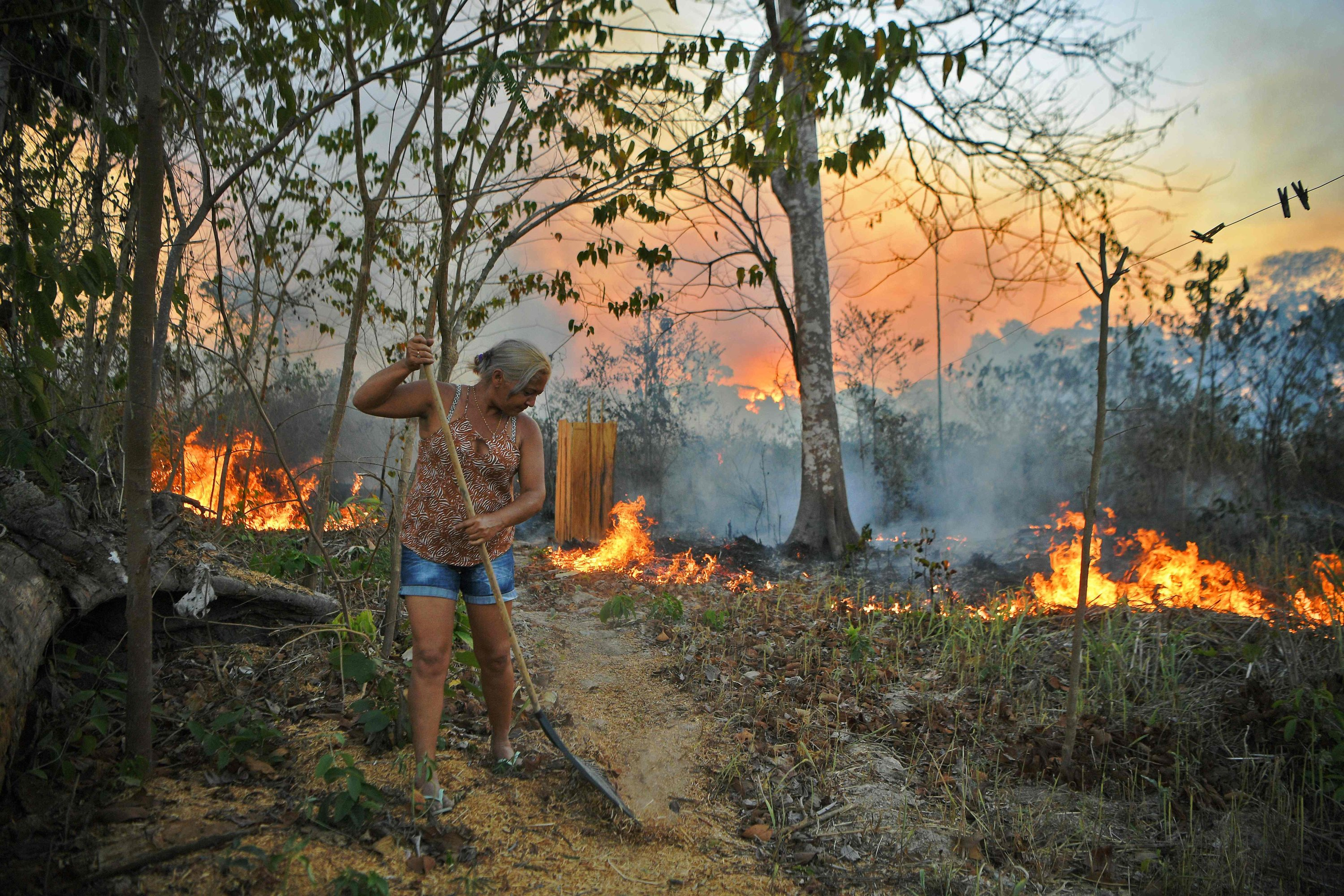 Idelia Lima Lisboa, wife of a farmer, tries to clear a path of dry leaves as the fire approaches their house in an area of Amazon rainforest, south of Novo Progresso in Para state, Brazil, Aug. 15, 2020. (AFP Photo)