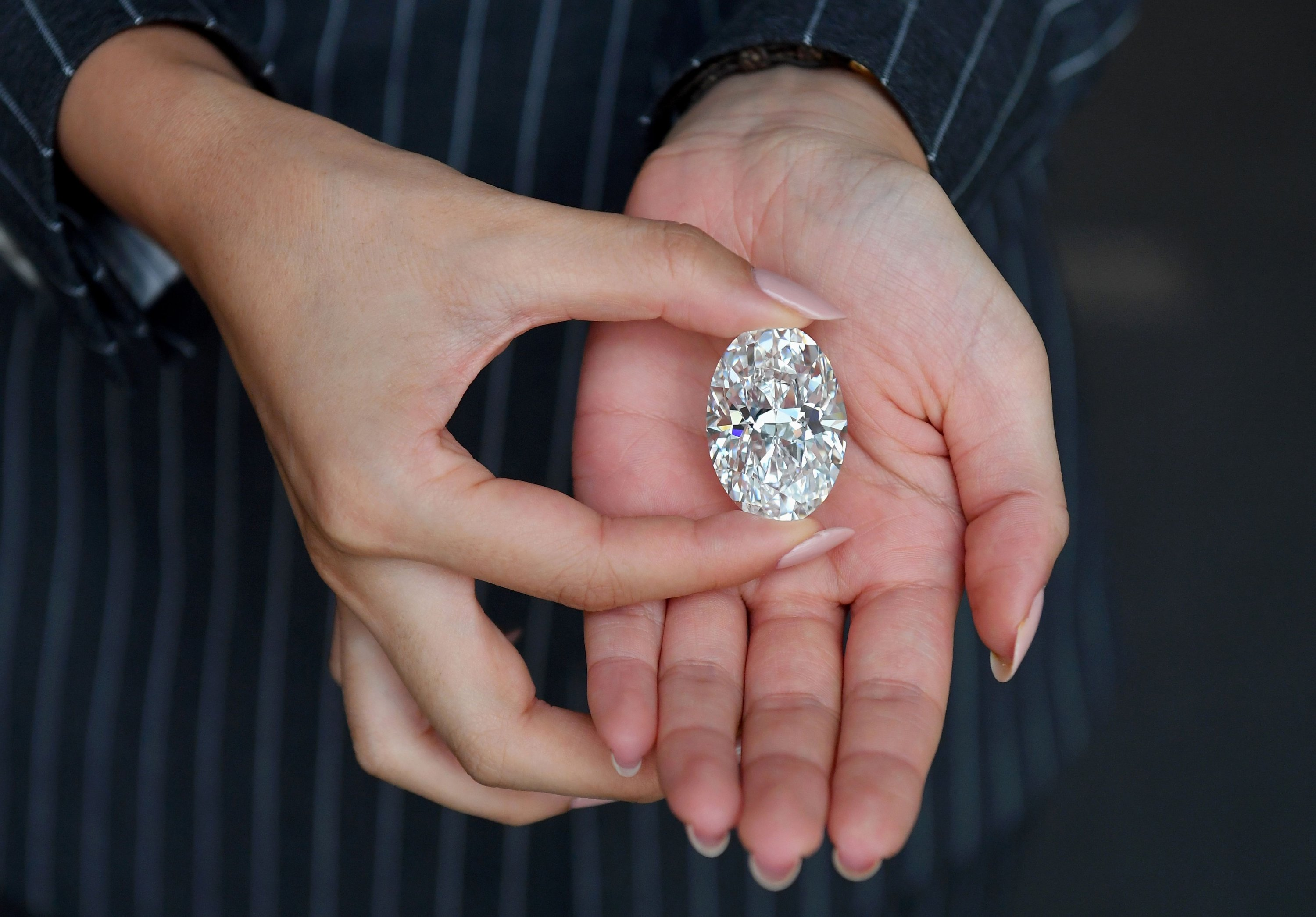 A Sotheby's employee holds a 102.39-carat flawless oval diamond during a media preview at Sotheby's, New York City, New York, U.S., Sept. 9, 2020. (AFP Photo)