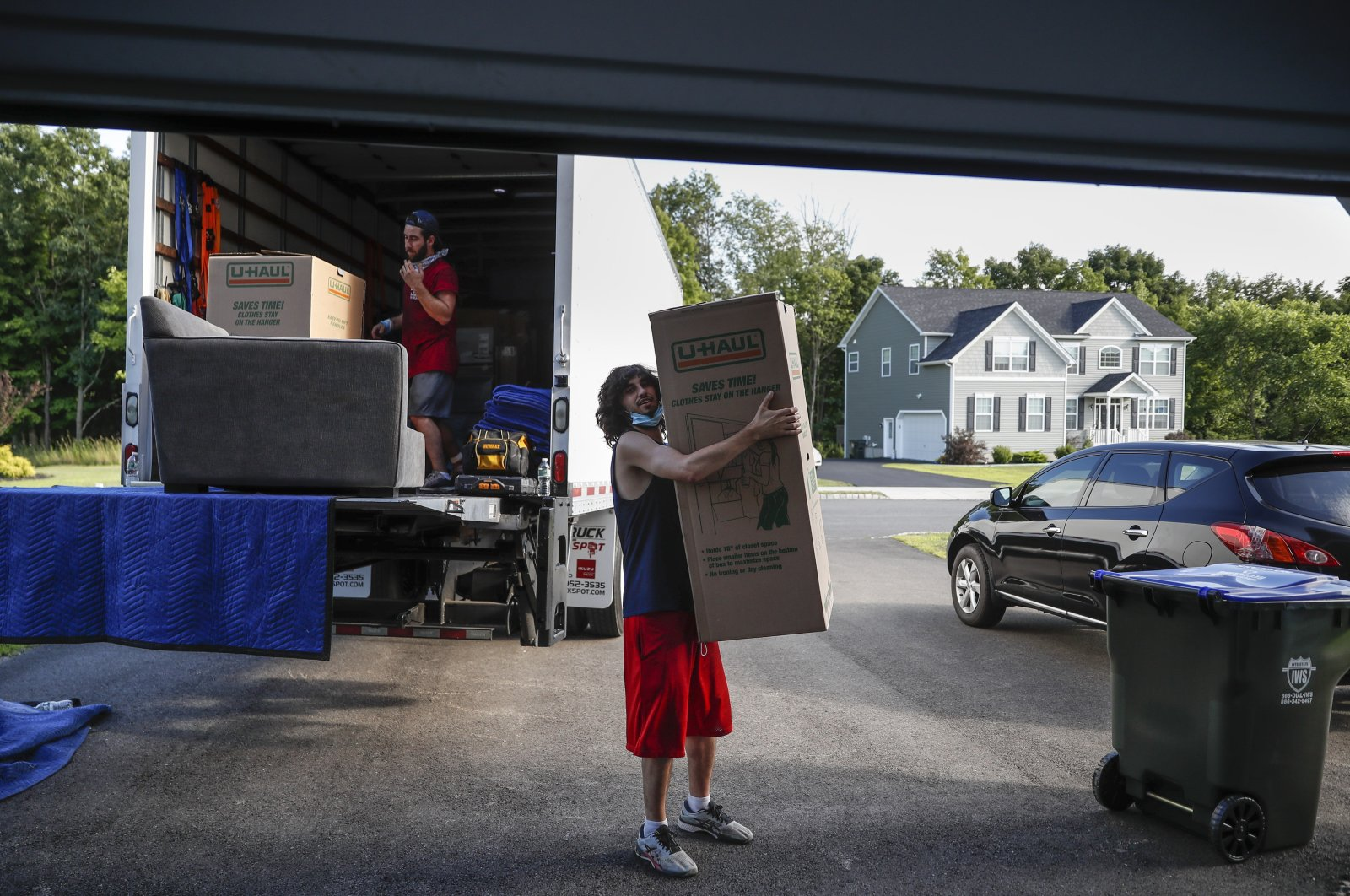 Movers unload a truckload of belongings as the Lilly family move into their new home, July 21, 2020, in Washingtonville, N.Y. (AP Photo)