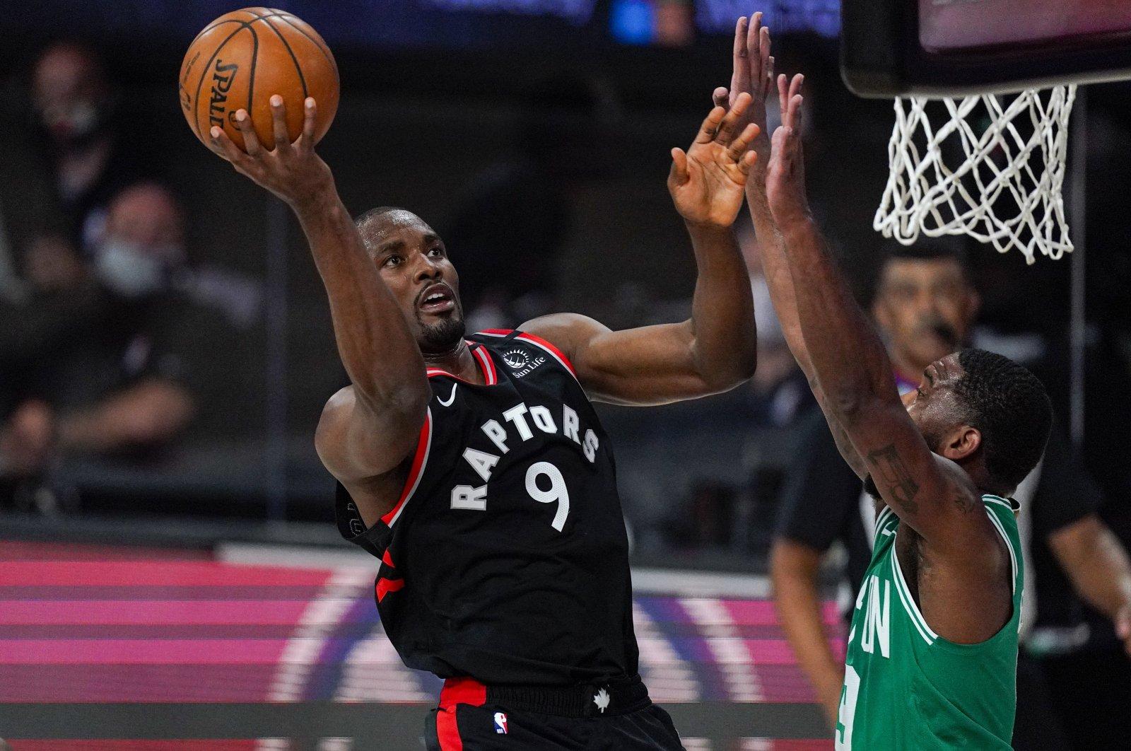 Toronto Raptors' Serge Ibaka (L) shoots over Boston Celtics' Brad Wanamaker during an NBA playoff basketball game in Lake Buena Vista, U.S., Sept. 9, 2020. (AP Photo)