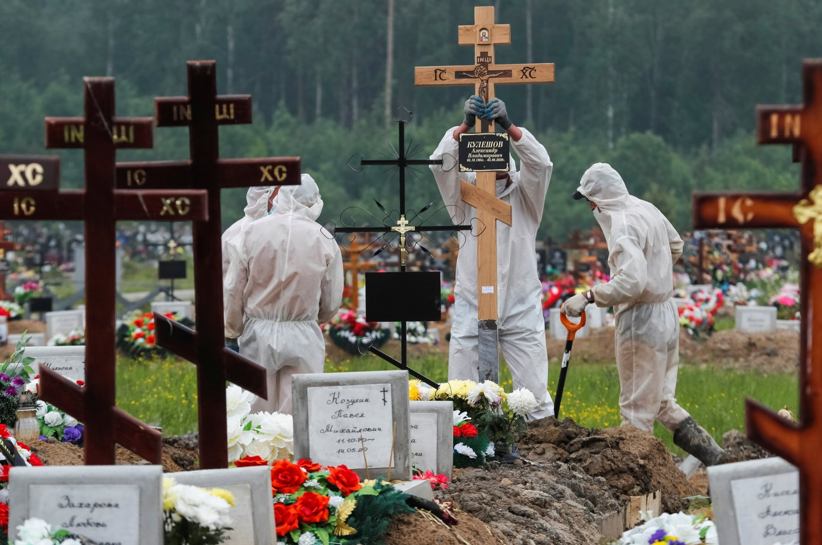 Grave diggers wearing personal protective equipment (PPE) bury a person, who presumably died of the coronavirus disease (COVID-19) in the special purpose section of a graveyard on the outskirts of Saint Petersburg, Russia on June 10, 2020. (Reuters Photo)