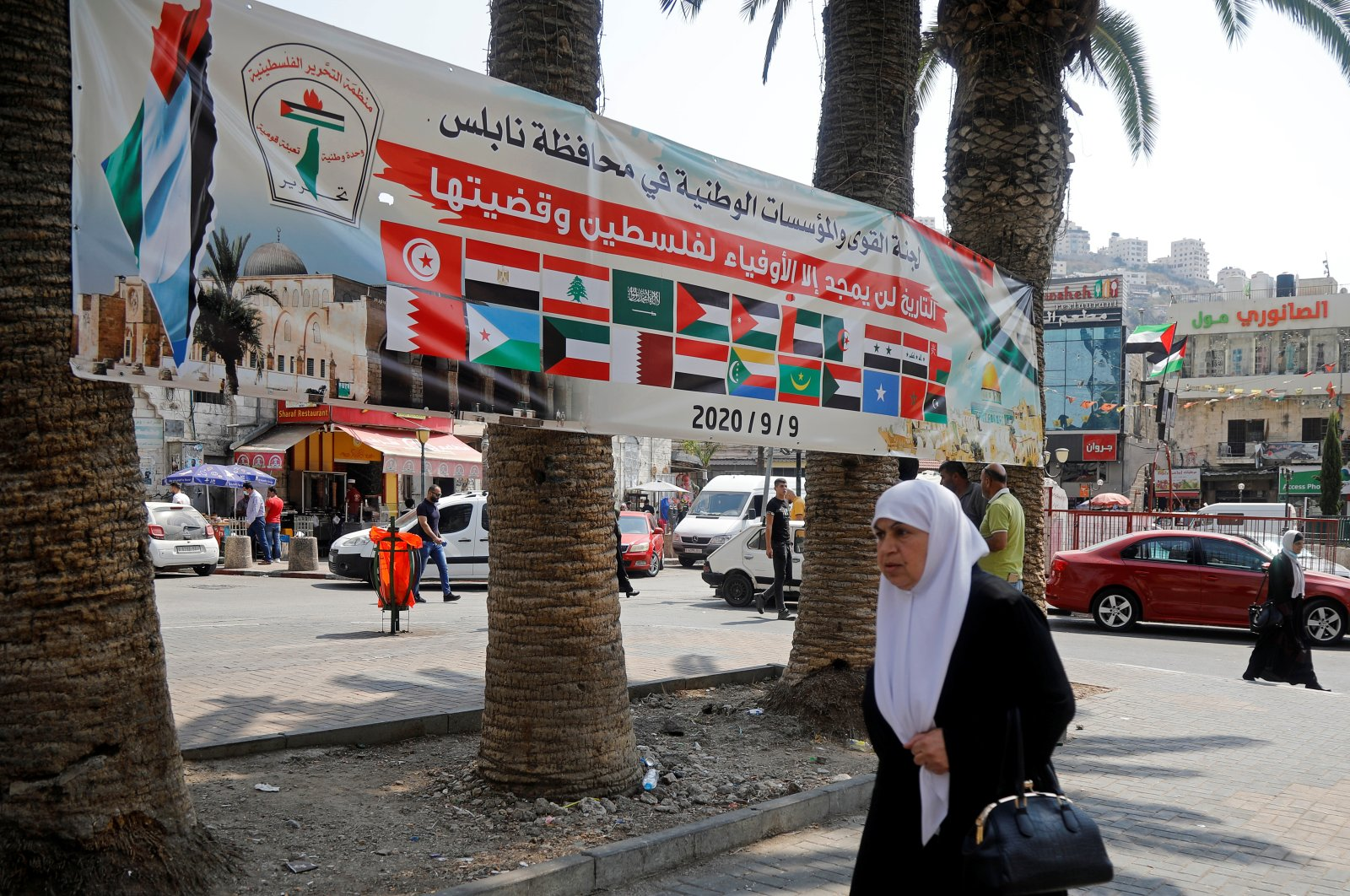 A woman walks past a banner showing Arab countries' flags during a protest against normalizing ties with Israel, in Nablus, in the Israeli-occupied West Bank, Sept. 9, 2020. (Reuters Photo)