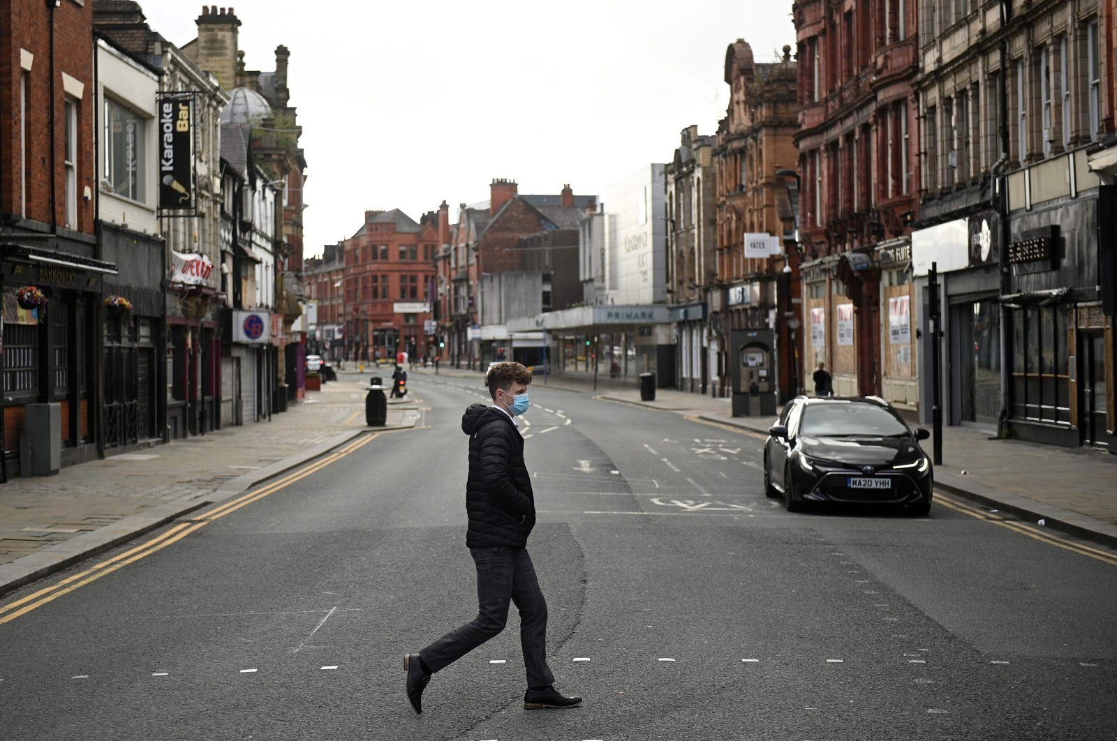 A man wearing a face mask due to the COVID-19 pandemic crosses an almost empty road in the center of Bolton, northern England, Sept. 9, 2020. (AFP Photo)