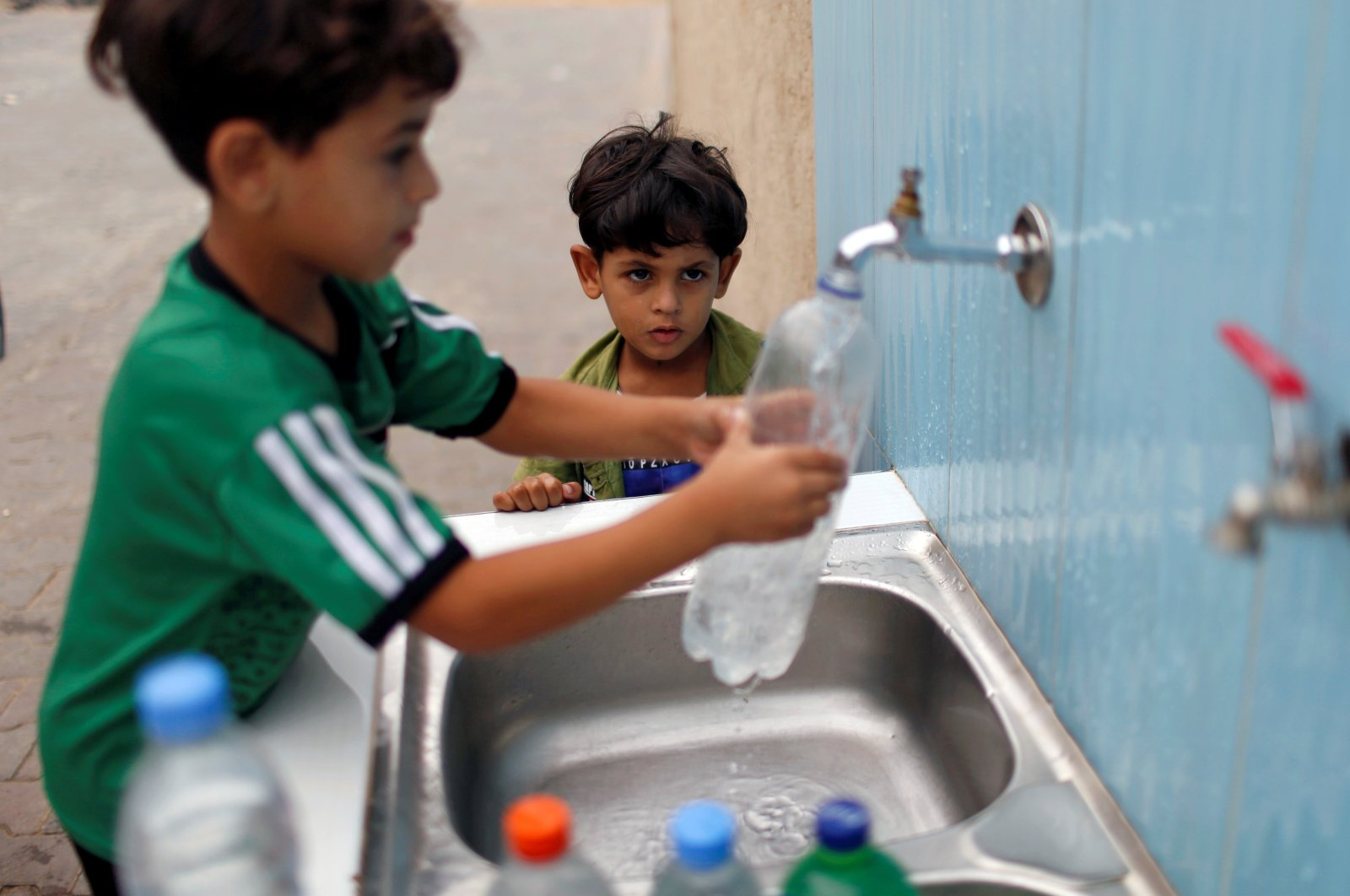 Palestinian boys fill bottles with water at a public tap during a lockdown amid the coronavirus outbreak, in Jabalia refugee camp in the northern Gaza Strip, Palestine, Sept. 10, 2020. (Reuters Photo)