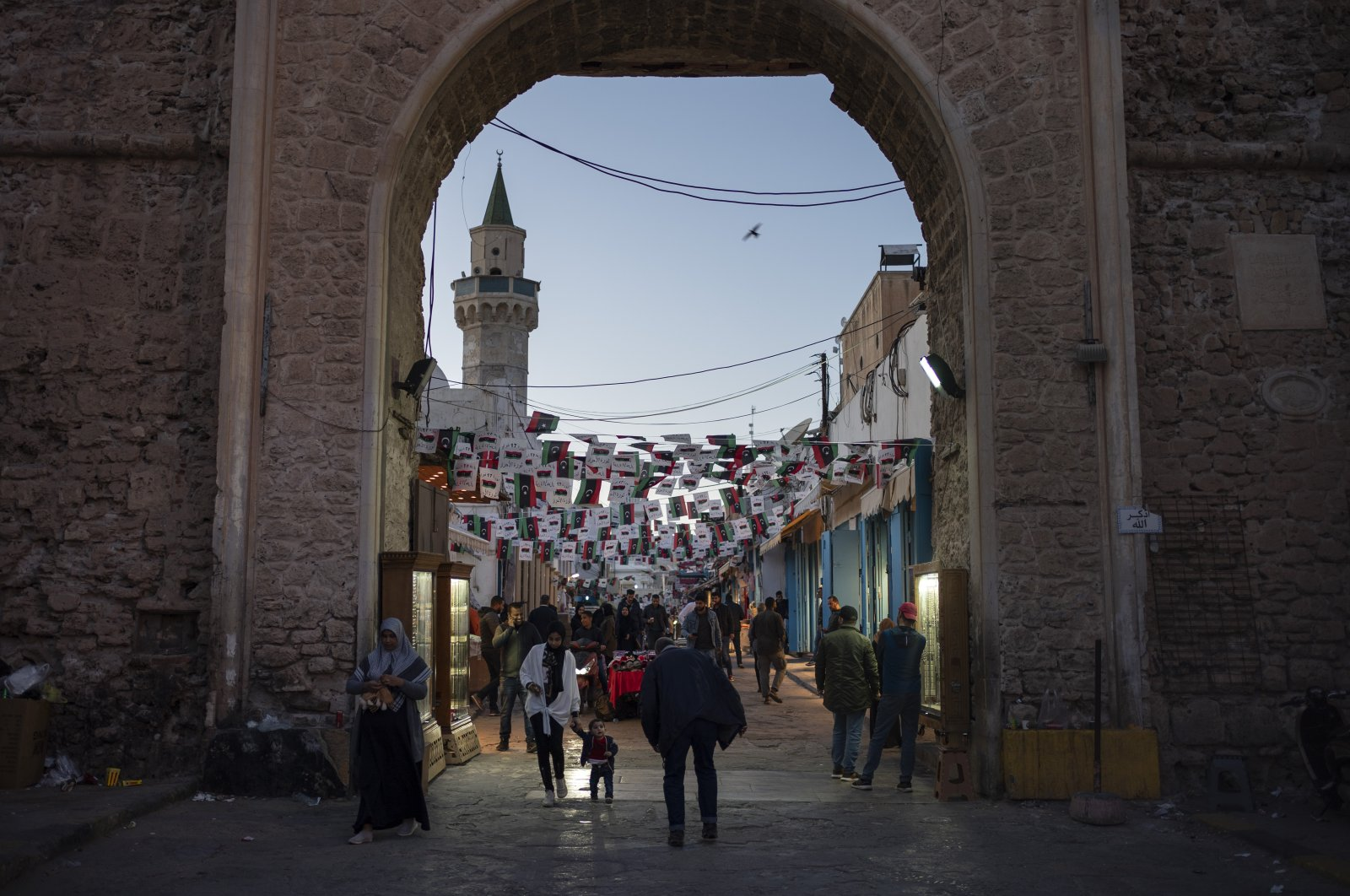 People walk near one of the entrances of the Old City in Tripoli, Libya, Feb. 25, 2020. (AP Photo)
