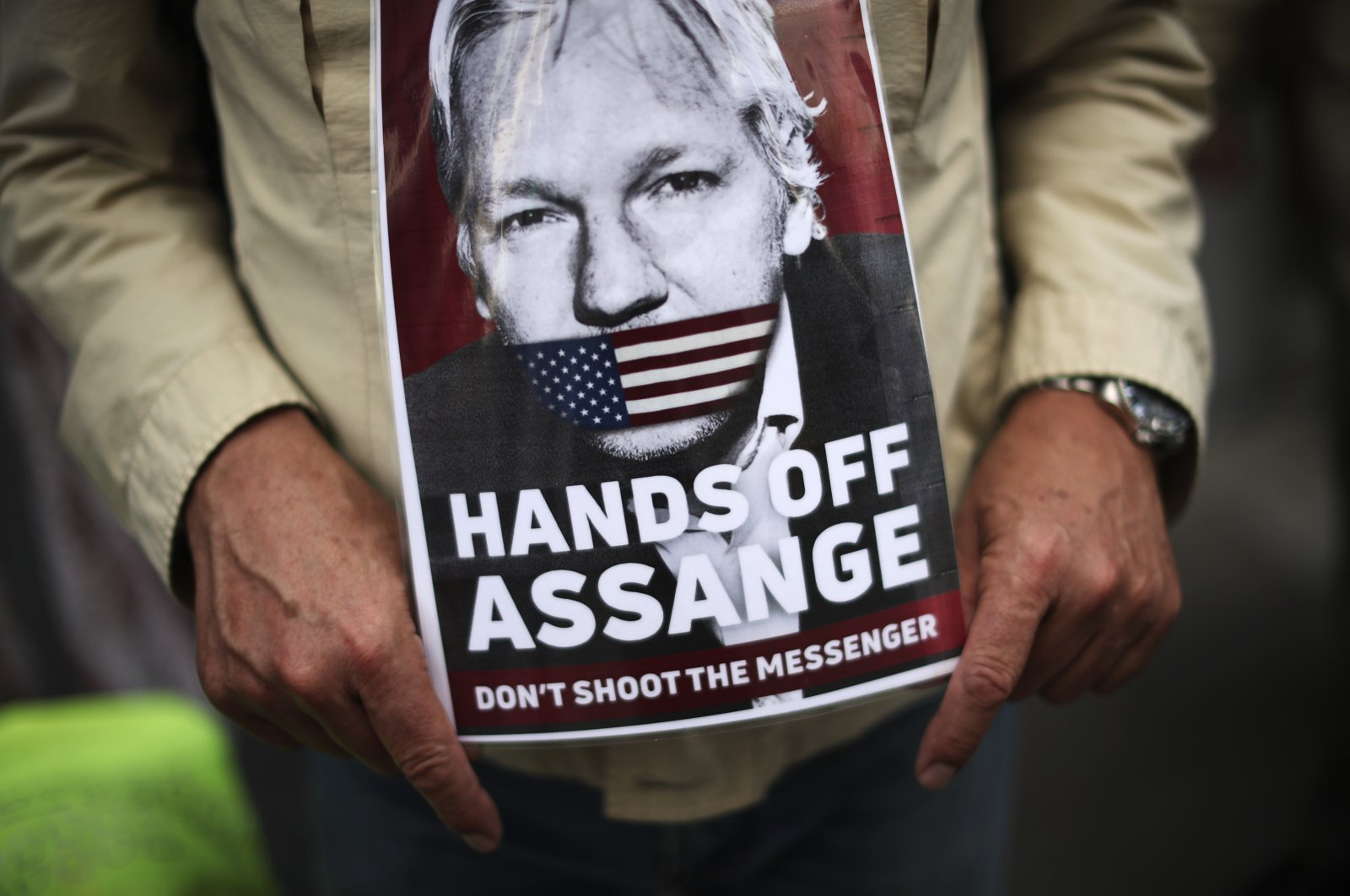 A man holds a photograph of WikiLeaks founder Julian Assange during a protest demanding the freedom of Assange in front of the U.K. embassy in Brussels, Sept. 7, 2020. (AP Photo)