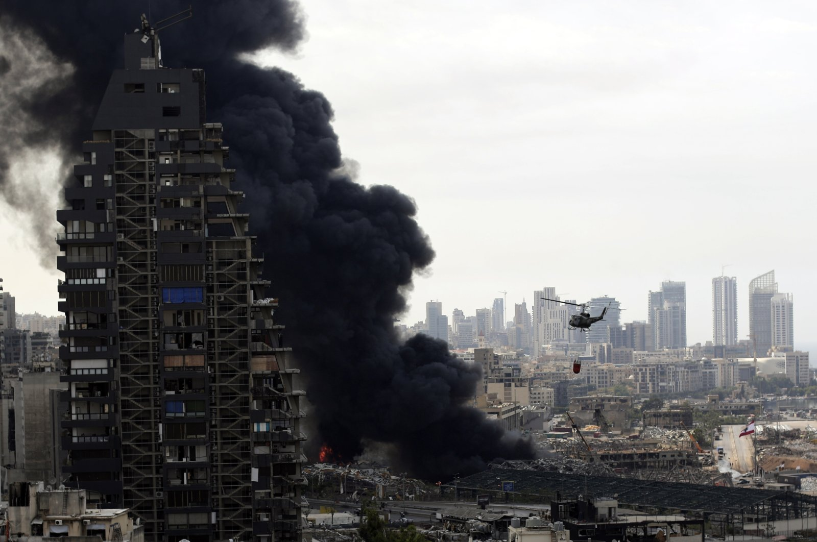 An army helicopter drops water on a fire at warehouses at the seaport in Beirut, Lebanon, Thursday, Sept. 10. 2020. (AP Photo)