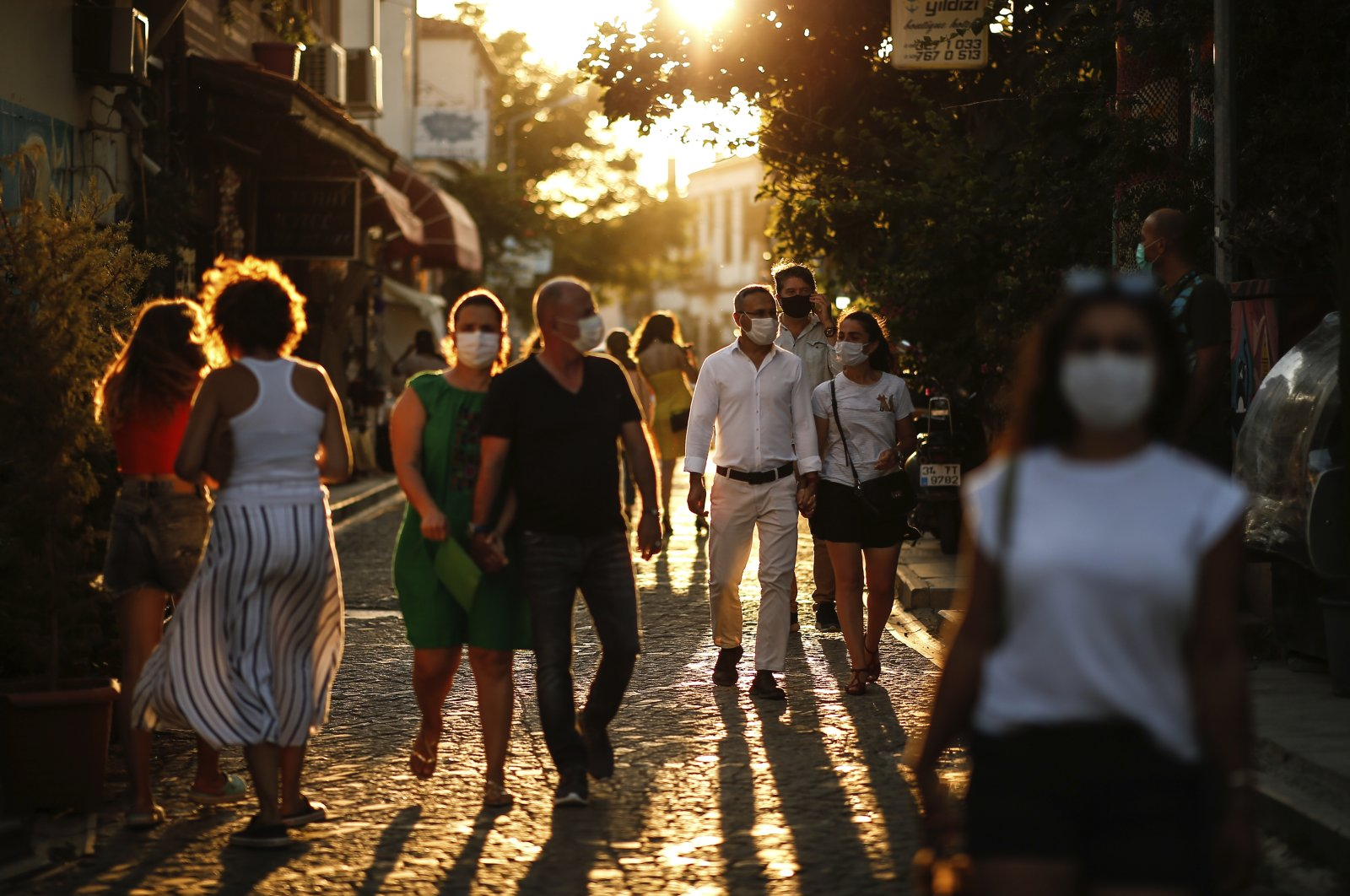 Tourists wearing protective masks walk on a street, in Ayvalık, a town in Balıkesir, western Turkey, Sept. 9, 2020. (AP Photo)