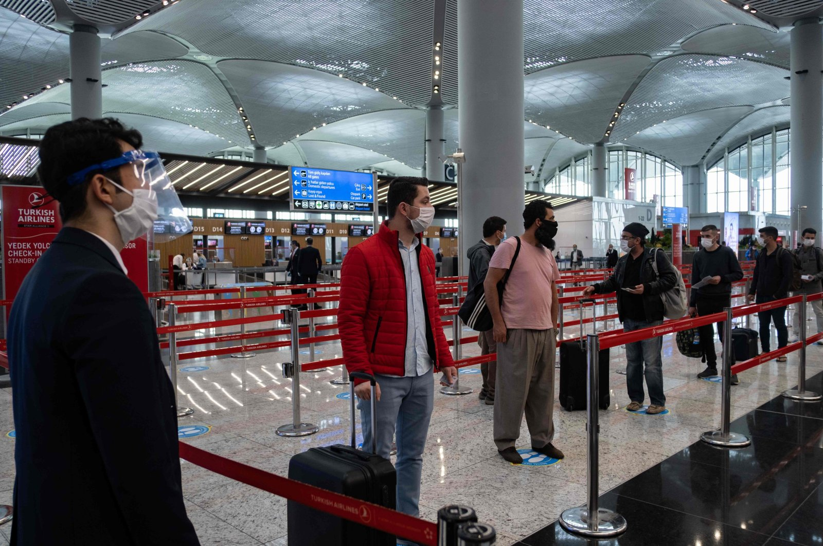 Passengers wearing protective face masks wait to be checked in at Istanbul Airport on the first day of the resumption of domestic flights after a pause due to the pandemic, in Istanbul, Turkey, June 1, 2020. (AFP Photo)