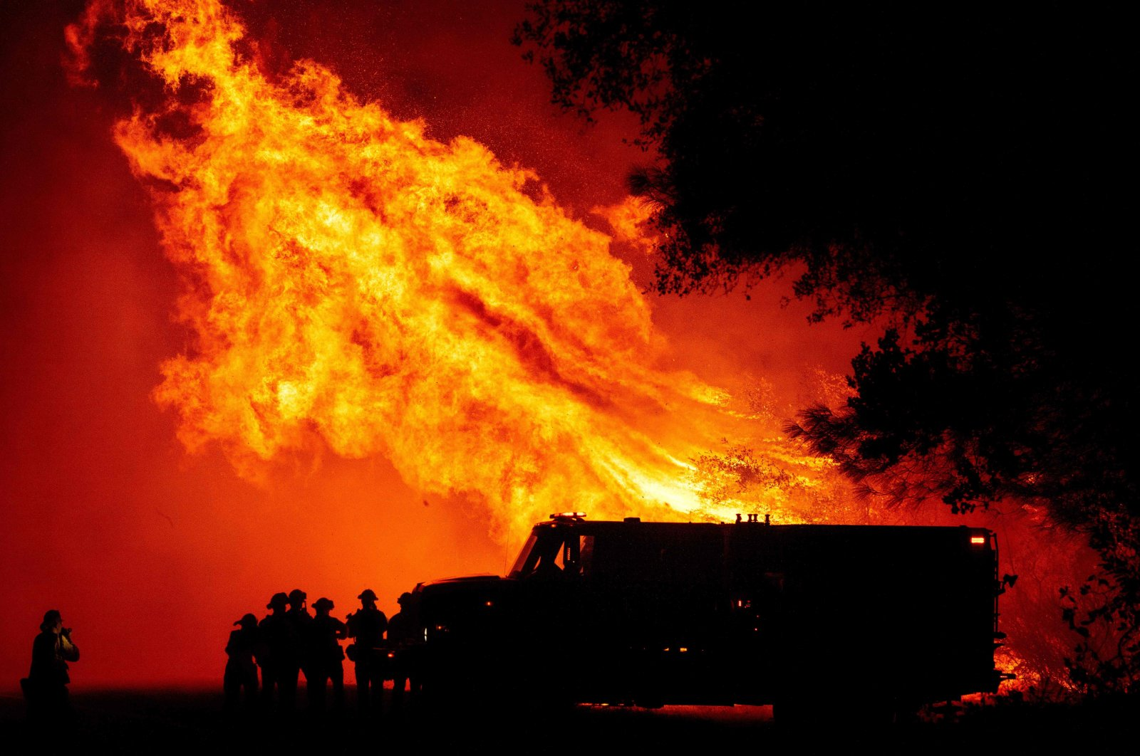 Butte county firefighters watch as flames tower over their truck during the Bear fire in Oroville, California, Sept. 9, 2020. (AFP)