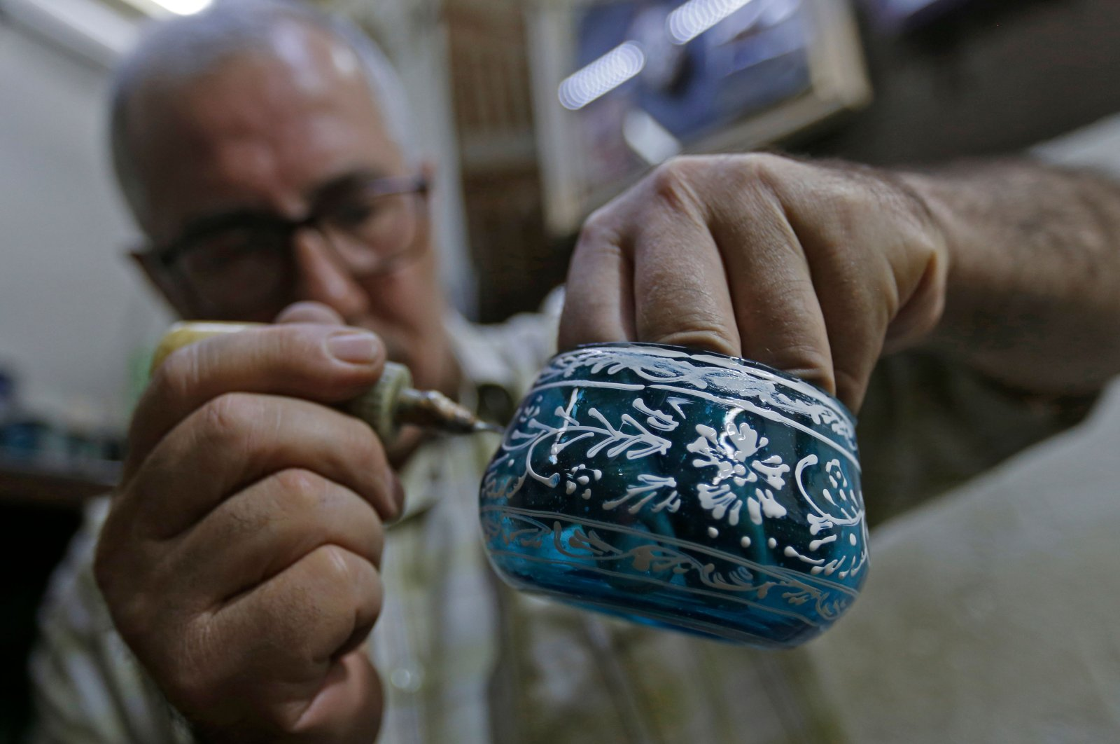Syrian Mohamed al-Hallak, 62, forms a votive in a glass-blowing workshop in Syria's capital Damascus, Aug. 26, 2020. (AFP Photo)