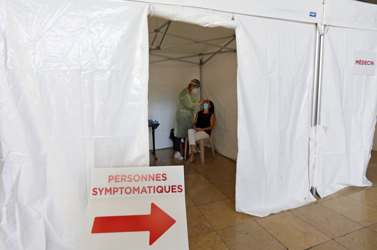 A medical worker, wearing protective suit and face mask, administers a nasal swab to a patient in a testing site, Nice, southern France Sept. 7, 2020. (REUTERS Photo)