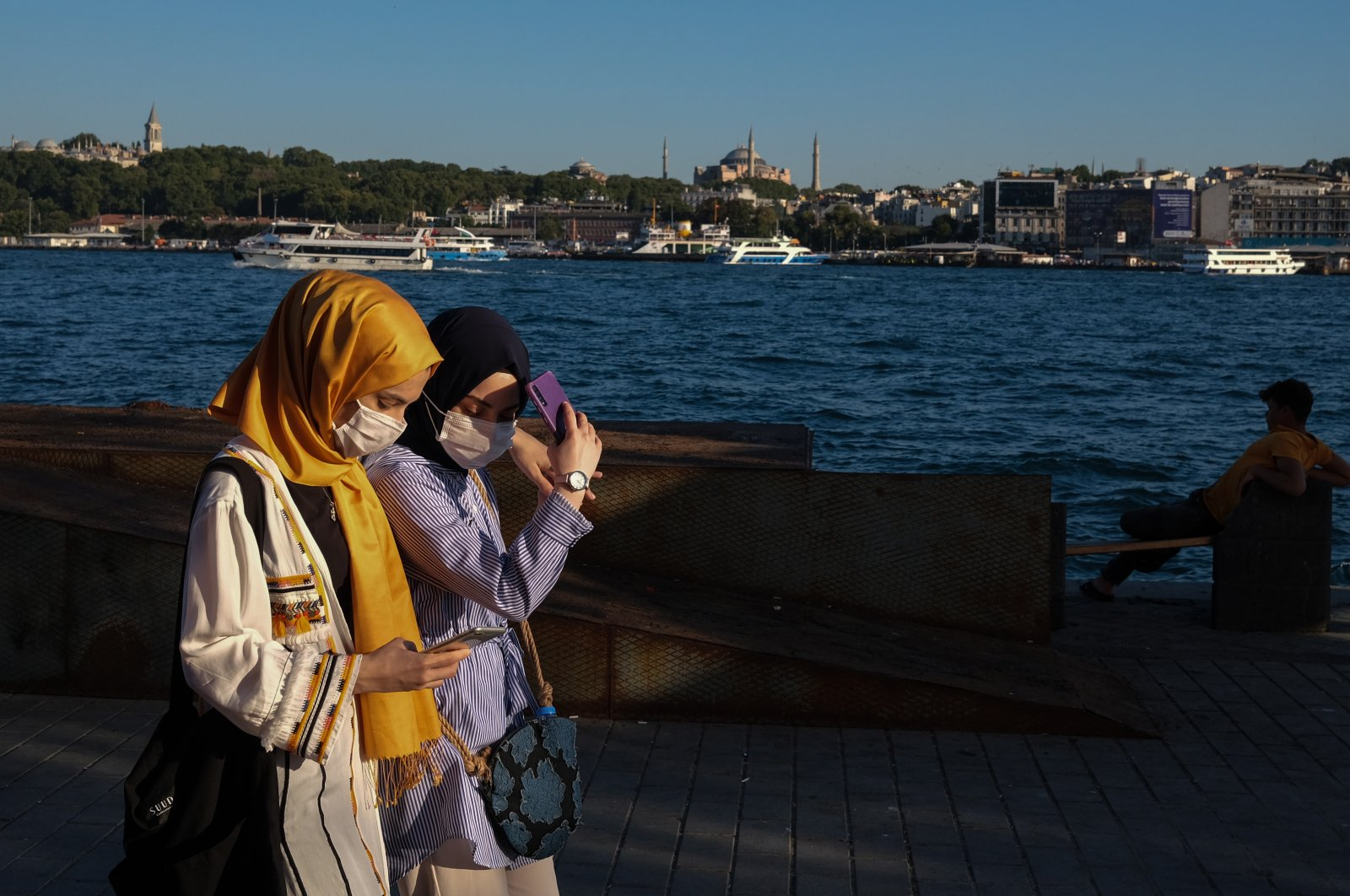 Women wearing face masks check their phones as they walk in Istanbul, Turkey, Aug. 12, 2020. (EPA Photo)