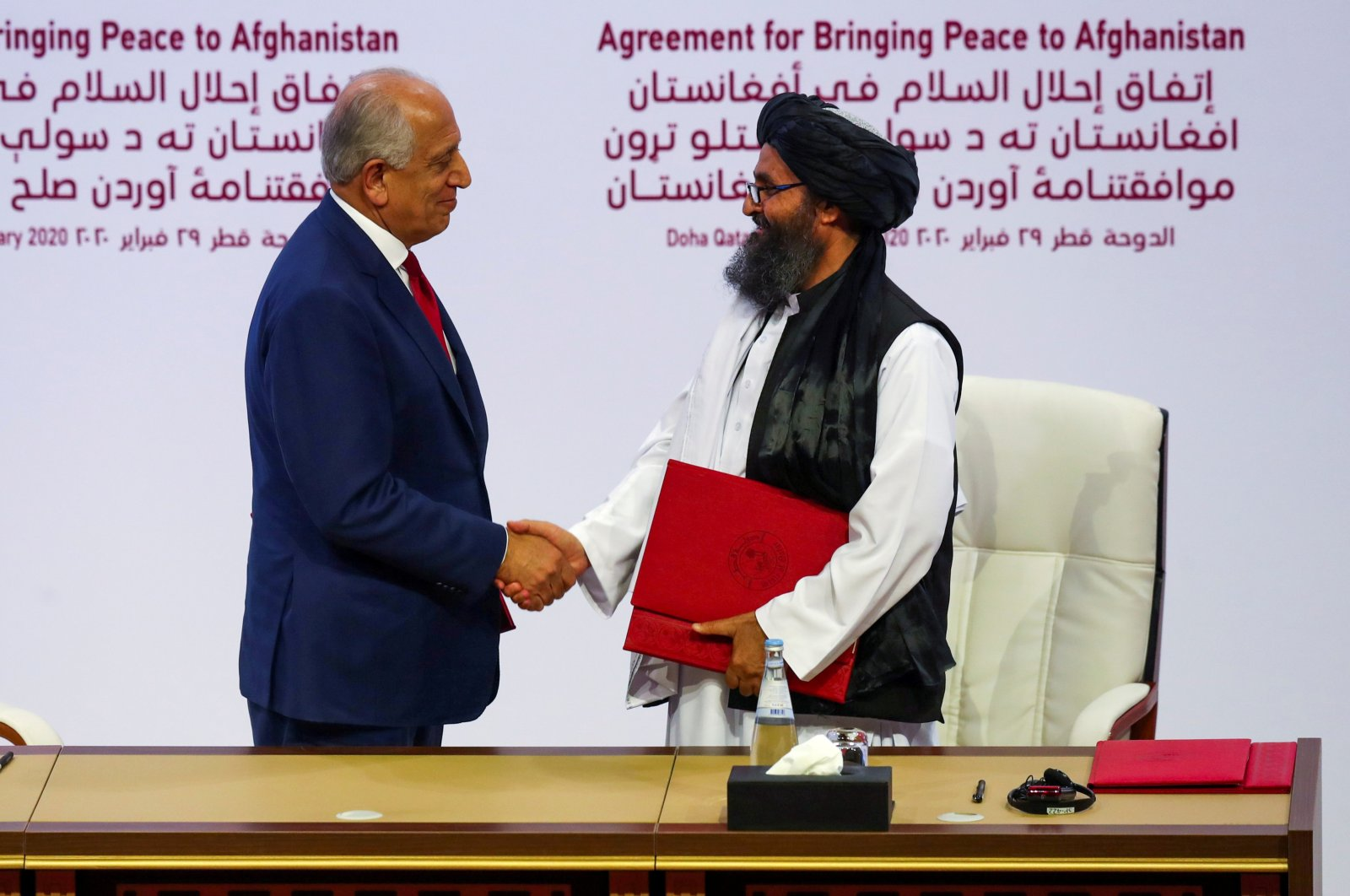 Leader of the Taliban delegation, Mullah Abdul Ghani Baradar (R), and U.S. envoy for peace in Afghanistan, Zalmay Khalilzad (L), shake hands after signing an agreement at a ceremony, Doha, Feb. 29, 2020. (REUTERS Photo)