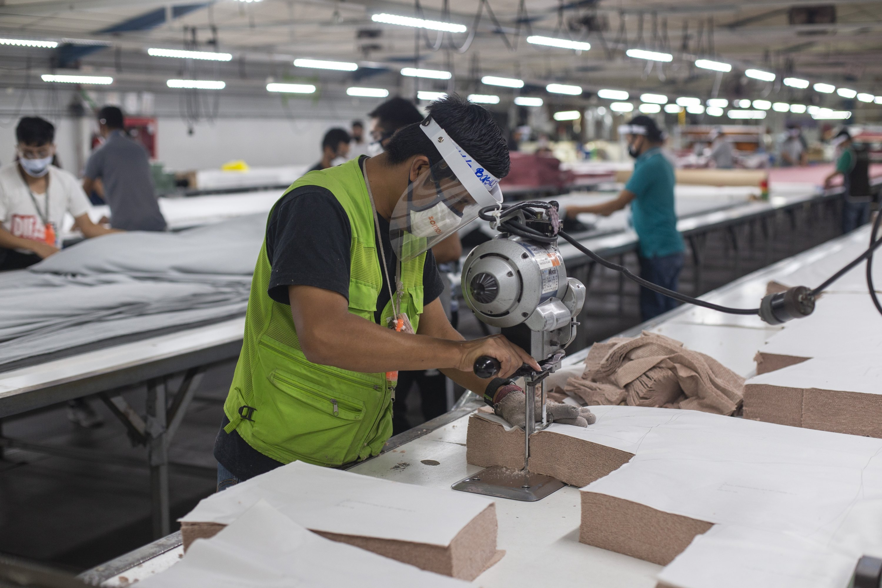 A worker, wearing a protective face mask and face shield, cuts T-shirt sections at the Korean-owned firm K.P. Textil in San Miguel Petapa, Guatemala, July 10, 2020. (AP Photo)
