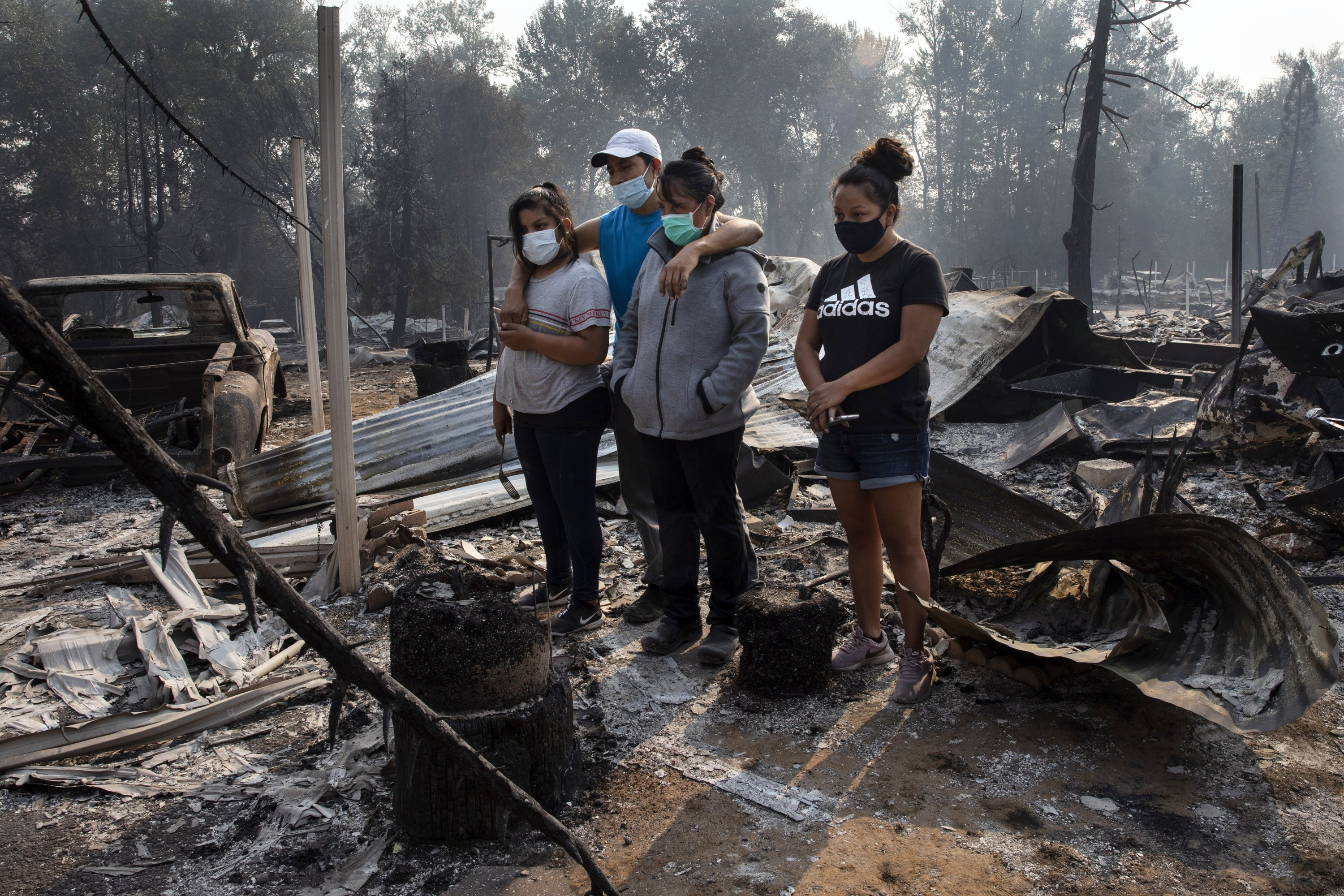 The Reyes family looks at the destruction of their home at Coleman Creek Estates mobile home park in Phoenix, Oregon, U.S., Sept. 10, 2020. (AP Photo)