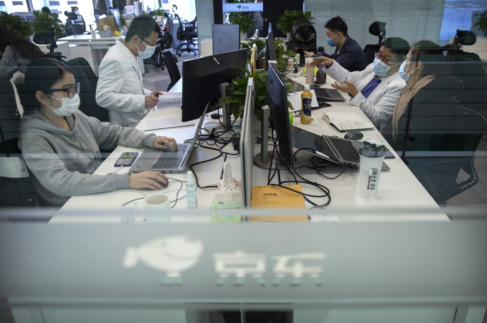 JD Health doctors use computers to chat online as they consult with patients at the JD.com headquarters in Beijing, China, March 27, 2020. (AP Photo)
