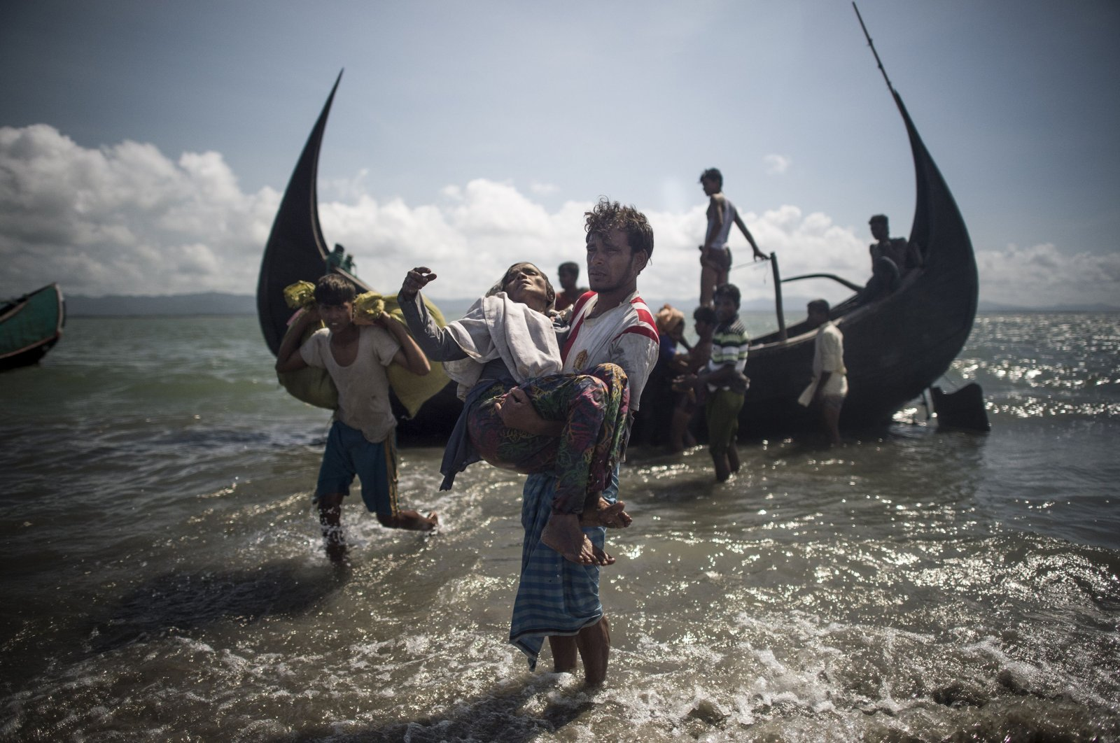 A Bangladeshi man helps Rohingya Muslim refugees to disembark from a boat on the Bangladeshi shoreline of the Naf river in Teknaf, after crossing the border from Myanmar, Sept. 30, 2017. (AFP Photo)