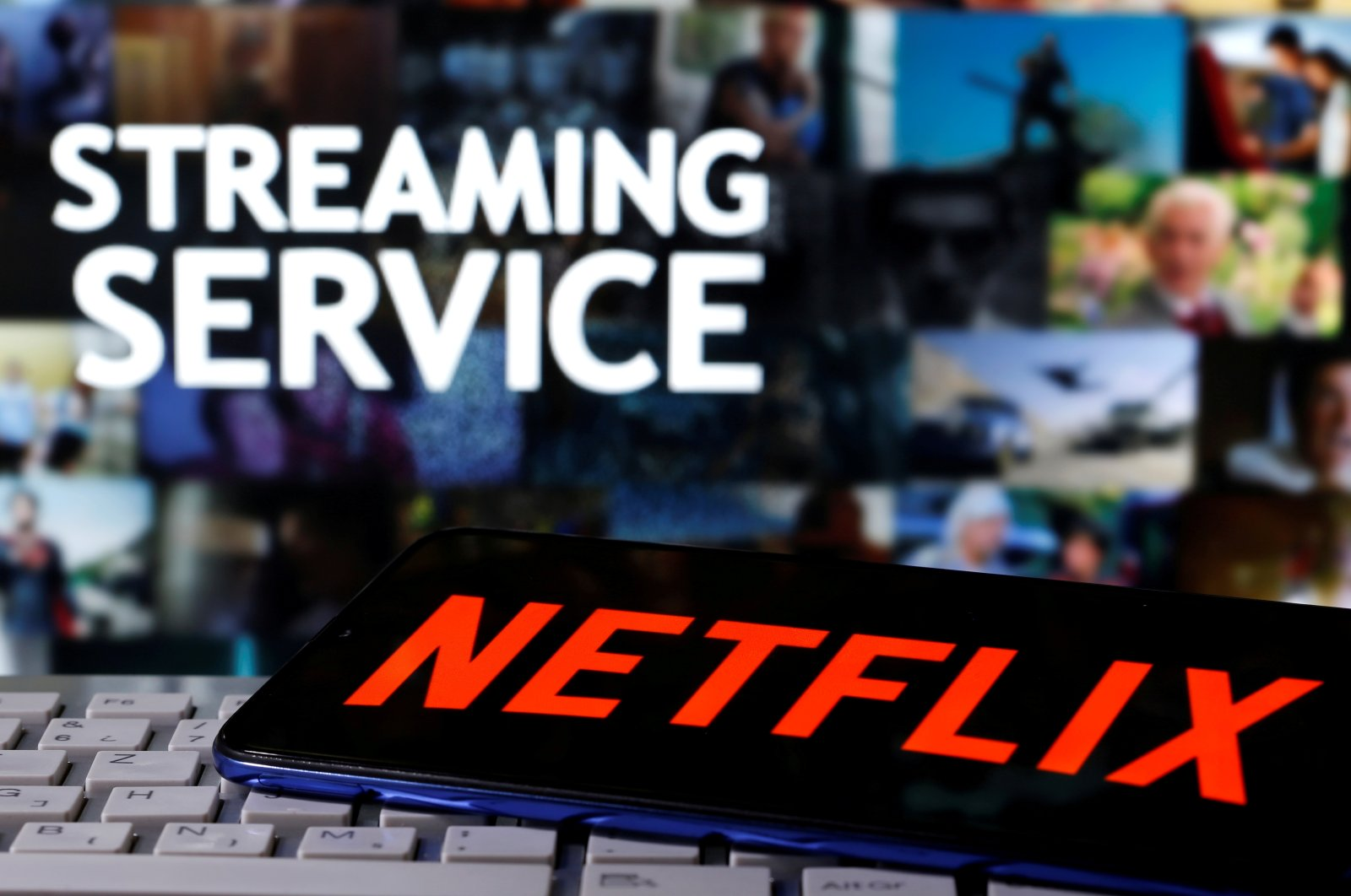 """A smartphone with the Netflix logo is seen on a keyboard in front of displayed """"Streaming service"""" words in this illustration taken March 24, 2020. (Reuters Photo)"""