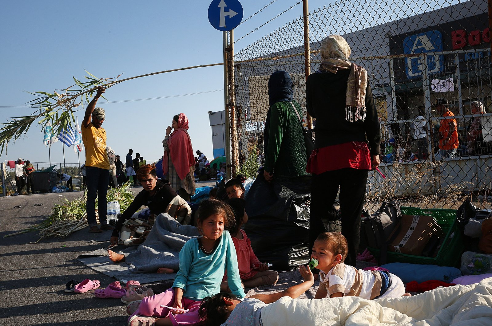 Asylum-seekers rest on the side of a road near the Moria refugee camp that was destroyed in a fire on Sept. 9, Lesbos island, Greece, Sept. 11, 2020. (EPA Photo)
