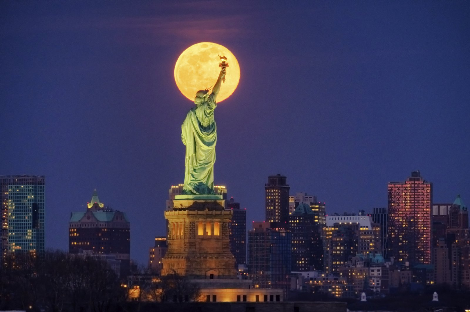 The full moon rises behind the Statue of Liberty in New York, March 9, 2020. (AP Photo)