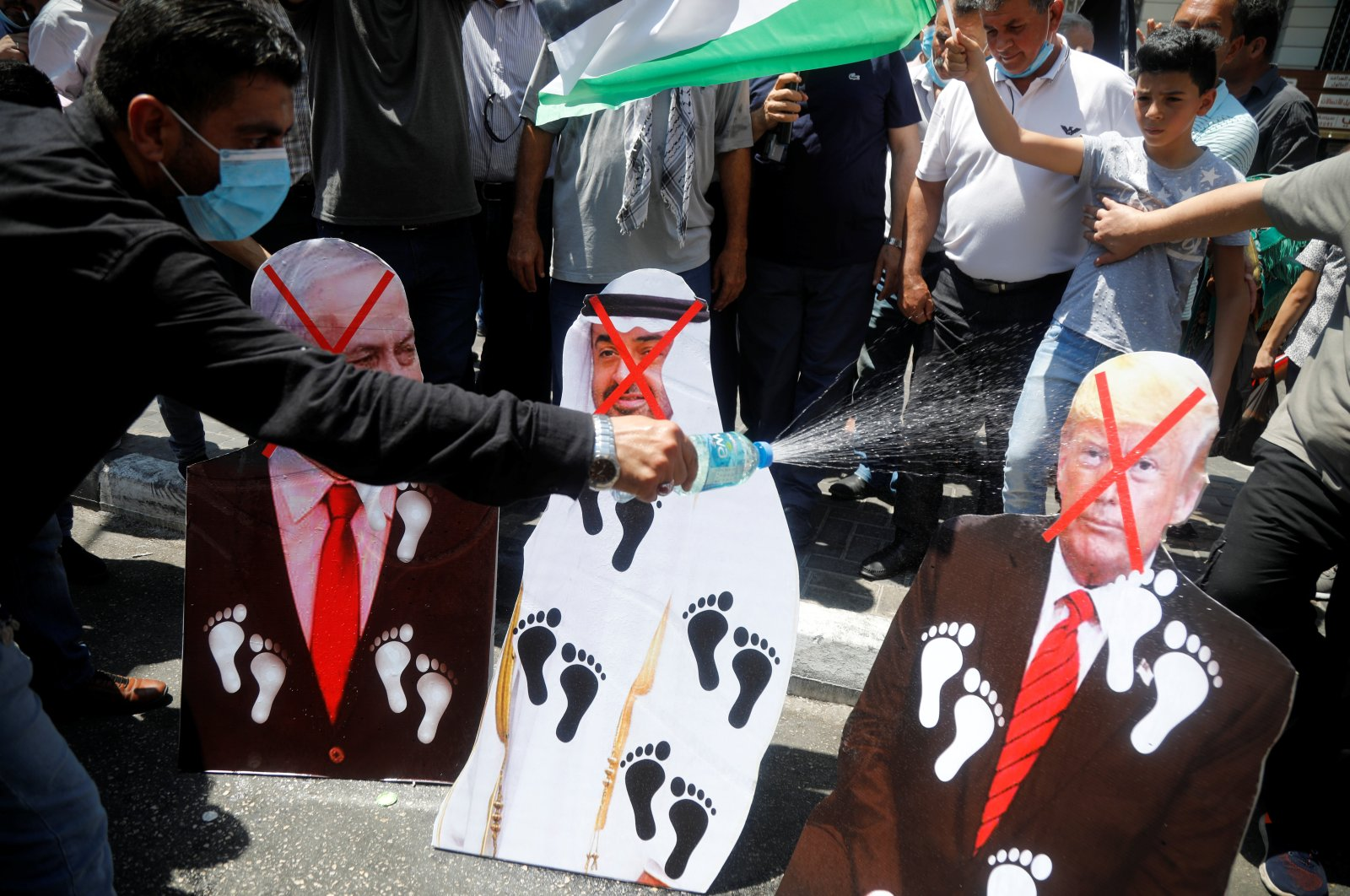 Palestinians burn cutouts depicting U.S. President Donald Trump, Abu Dhabi Crown Prince Mohammed bin Zayed al-Nahyan and Israeli Prime Minister Benjamin Netanyahu during a protest against the United Arab Emirates' (UAE) deal with Israel to normalize relations, in Nablus in the Israeli-occupied West Bank, Aug. 14, 2020. (Reuters Photo)