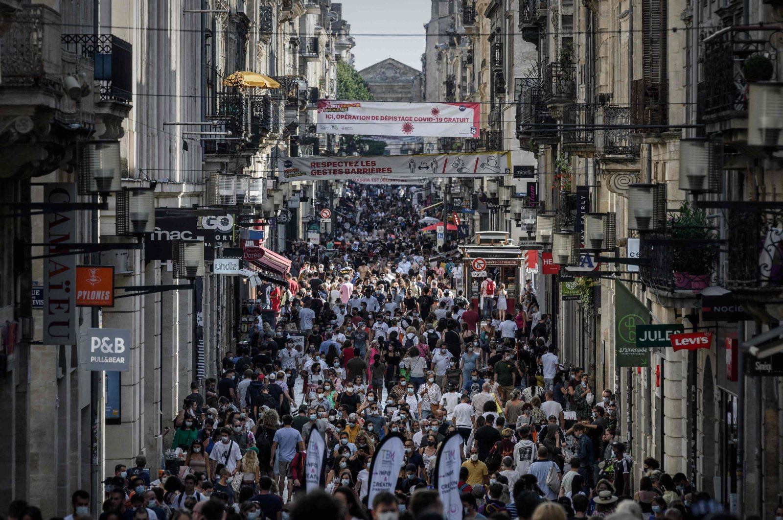 Pedestrians, some of them wearing protective face masks, walk along a street lined with shops, Bordeaux, France, Sept. 5, 2020. (AFP Photo)