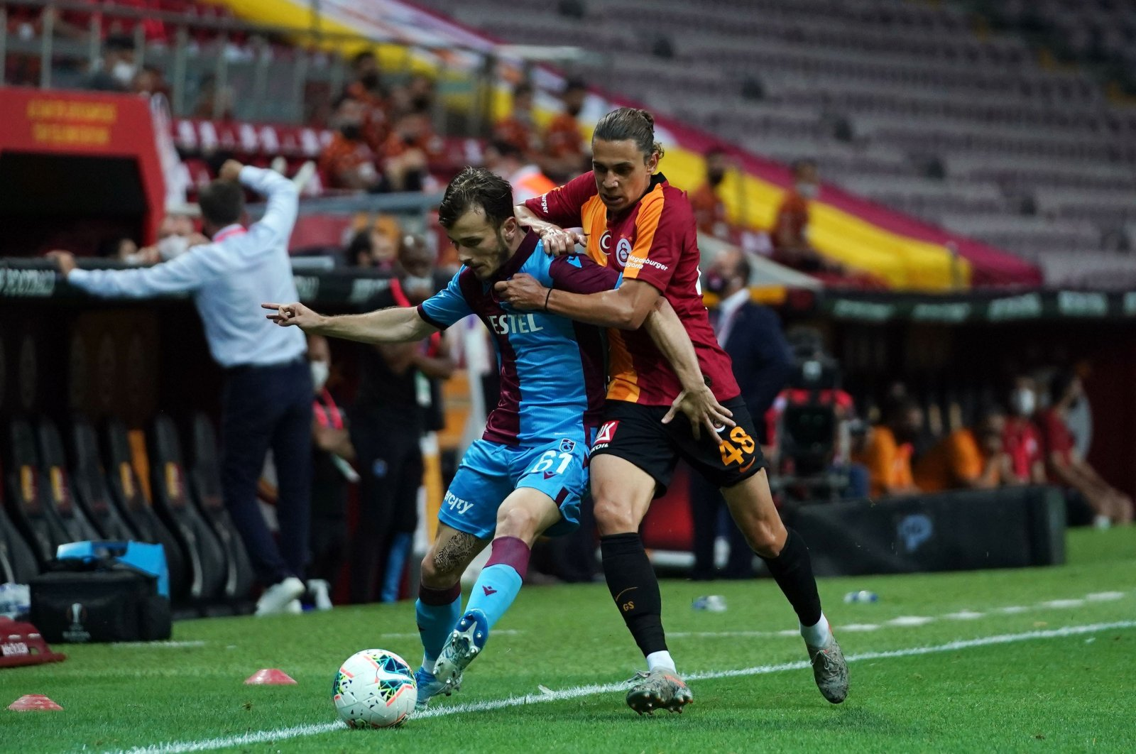 Trabzonspor's Abdülkadir Parmak and Galatasaray's Taylan Antalyalı compete for the ball during a Süper Lig match in Istanbul, Turkey, July 5, 2020. (IHA Photo)