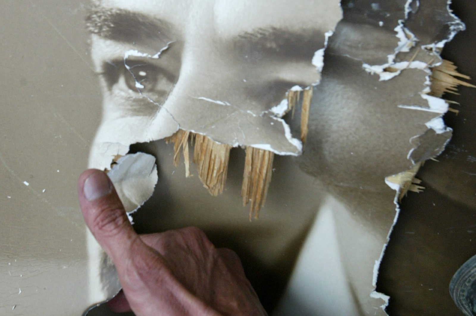 An Iraqi burns a torn picture of late leader Saddam Hussein in the capital Baghdad, Iraq, April 9, 2003. (AFP Photo)