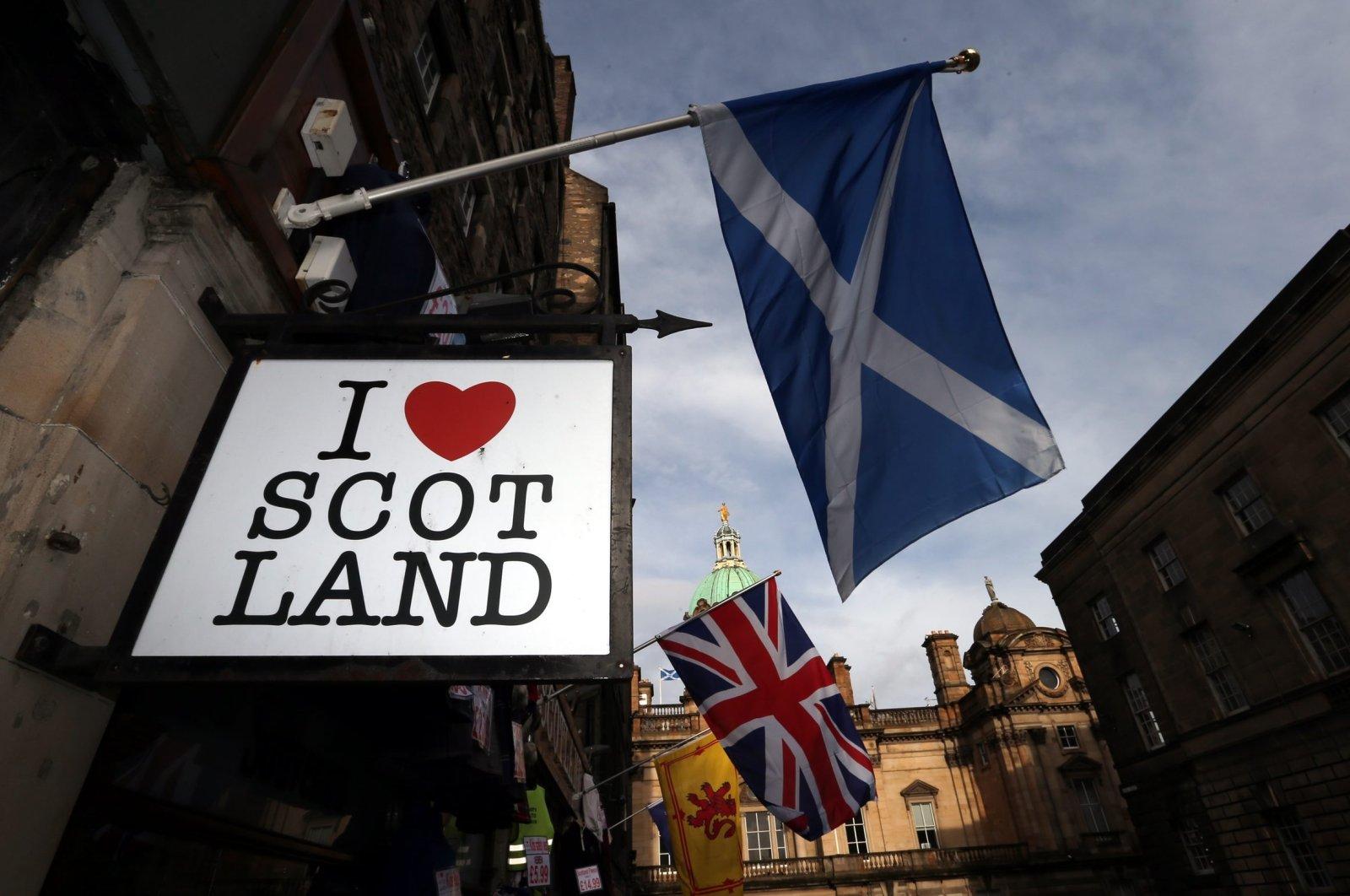 In this Thursday, Feb. 13, 2014, file photo a Scottish flag and a Union flag fly outside a Scottish memorabilia shop in Edinburgh, Scotland. (AP Photo)