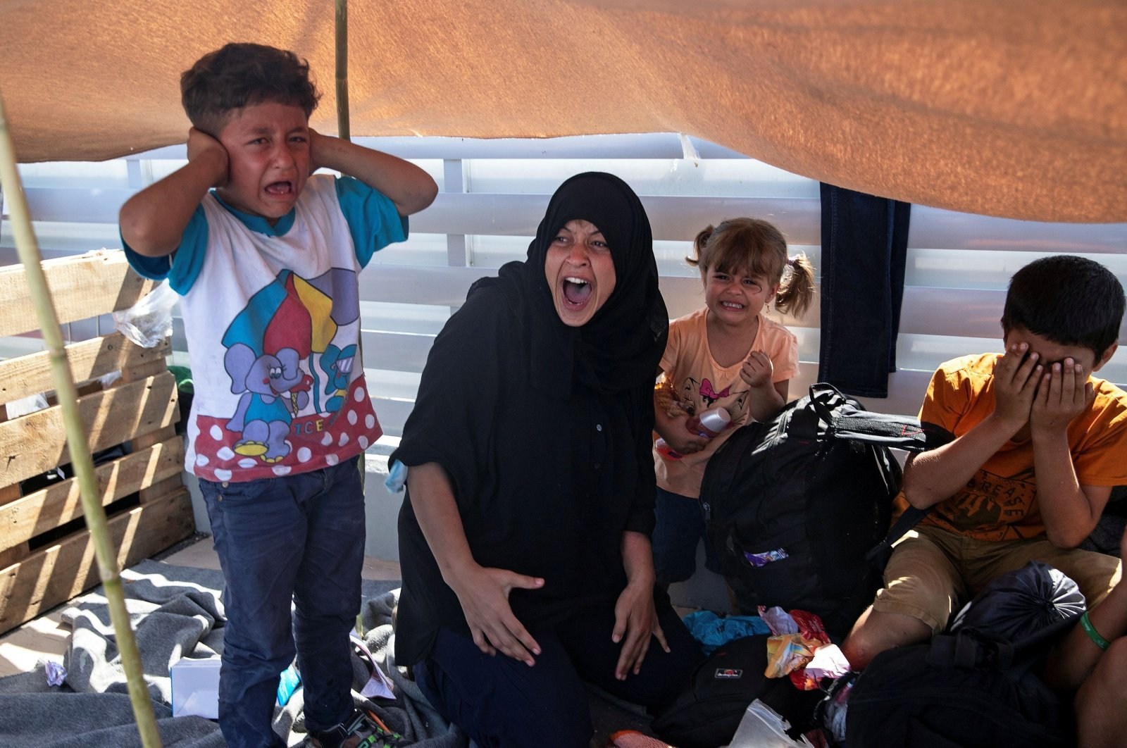Woman and children react as refugees and migrants from the destroyed camp of Moria flee clash with the police, on the island of Lesbos, Greece, Sept. 12, 2020. (Reuters Photo)
