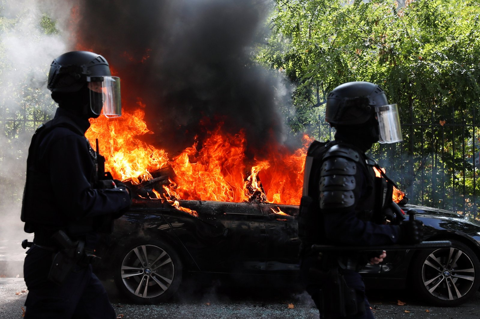 French CRS riot police officers walk past a burning car during a demonstration of the yellow vests movement in Paris, France Sept. 12, 2020. (Reuters Photo)