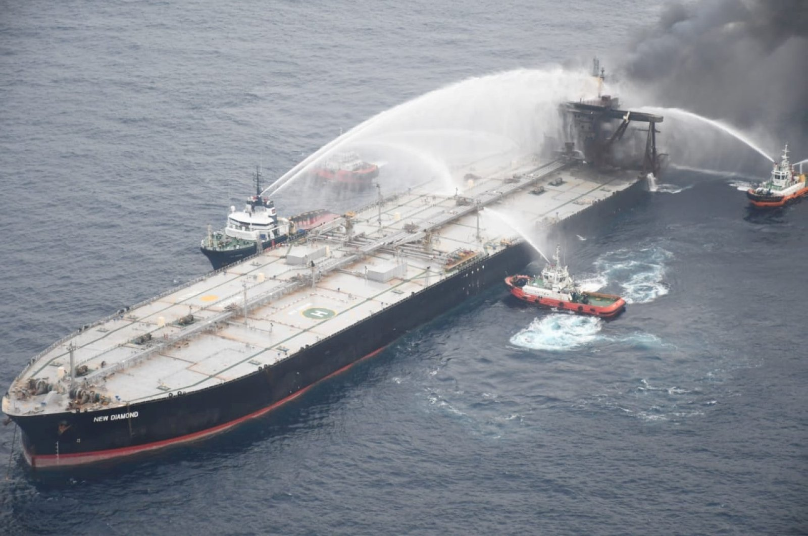 A Sri Lankan Navy boat sprays water on the New Diamond, a very large crude carrier (VLCC) chartered by Indian Oil Corp (IOC), that was carrying the equivalent of about 2 million barrels of oil, after a fire broke out off east coast of Sri Lanka Sept. 8, 2020. (Reuters Photo)