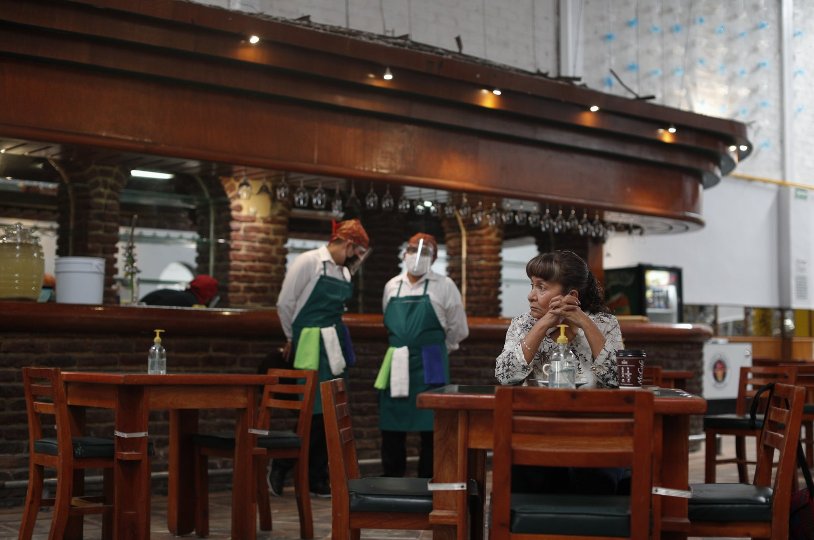 The very first customer sits at a table in Que Viva Mexico, a casual traditional food restaurant that opened its doors amid the ongoing coronavirus pandemic, in central Mexico City, Sept. 1, 2020. (AP Photo)
