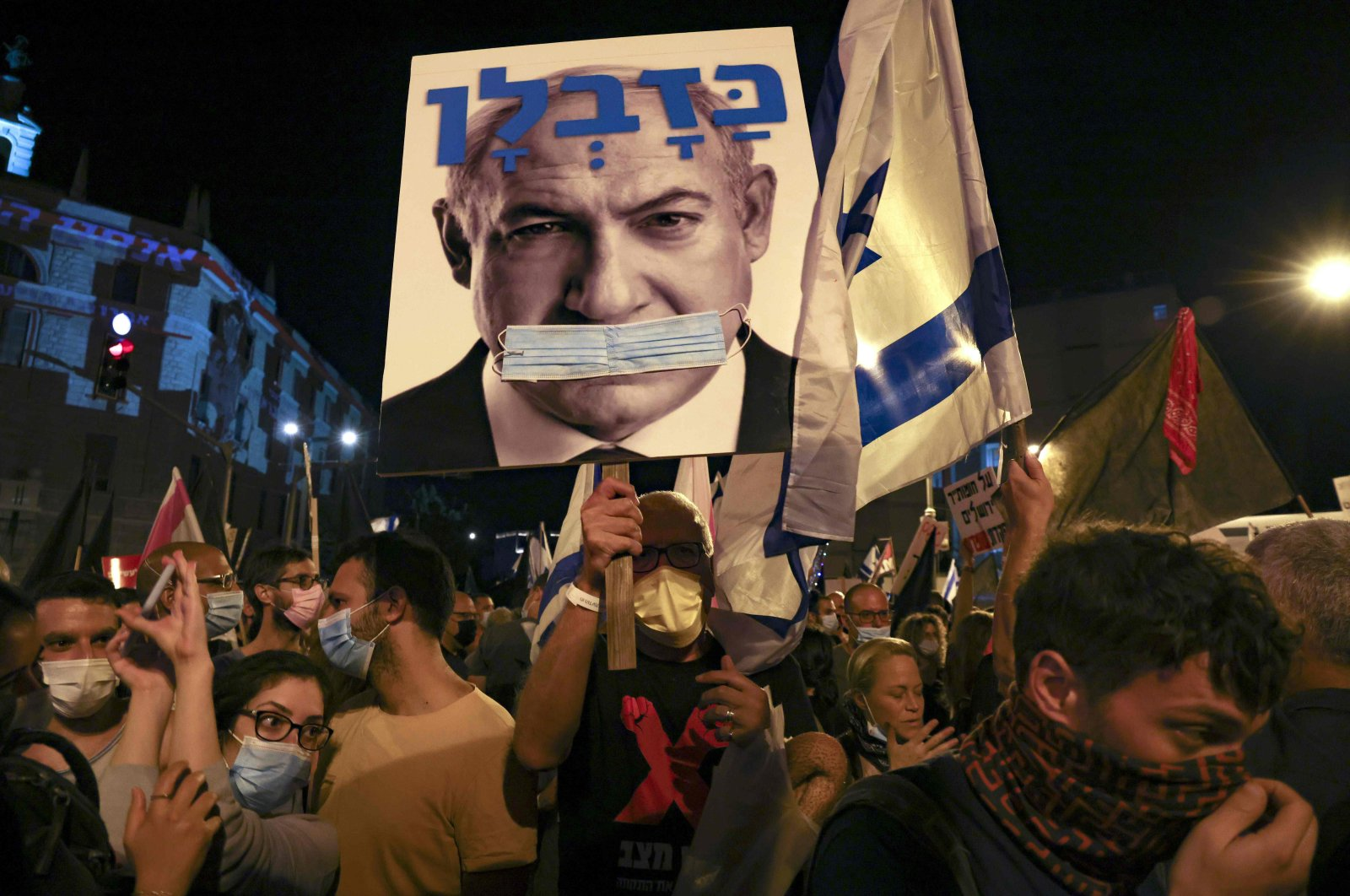 Israeli protesters hold a poster depicting their Prime Minister Benjamin Netanyahu gagged by a surgical protection mask in front of Netanyahu's residence, Jerusalem, Sept. 12, 2020. (AFP Photo)
