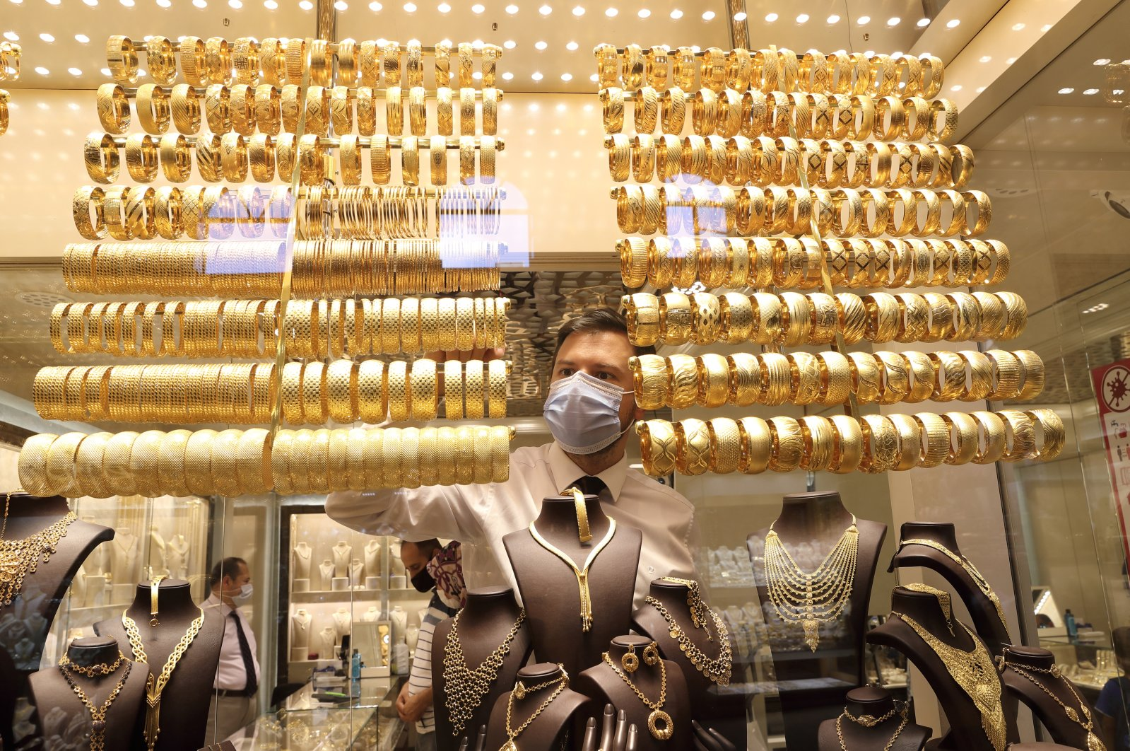 A goldsmith wearing a protective face mask arranges golden bangles as the other talks to customers at a jewelry shop at the Grand Bazaar in Istanbul, Turkey, Aug. 6, 2020. (Reuters Photo)