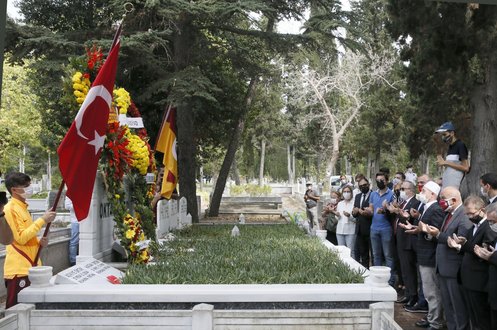 People holding Turkish and Galatasaray flags pray at Oktay's grave, in Istanbul, Turkey, Sept. 13, 2020. (AA Photo)
