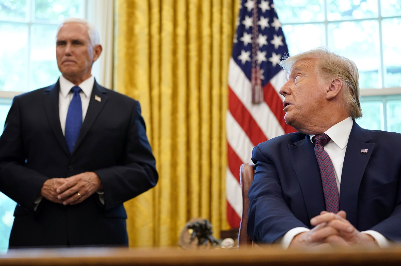 U.S. President Donald Trump looks toward Vice President Mike Pence in the Oval Office of the White House, Washington, D.C., Sept. 11, 2020. (AP Photo)
