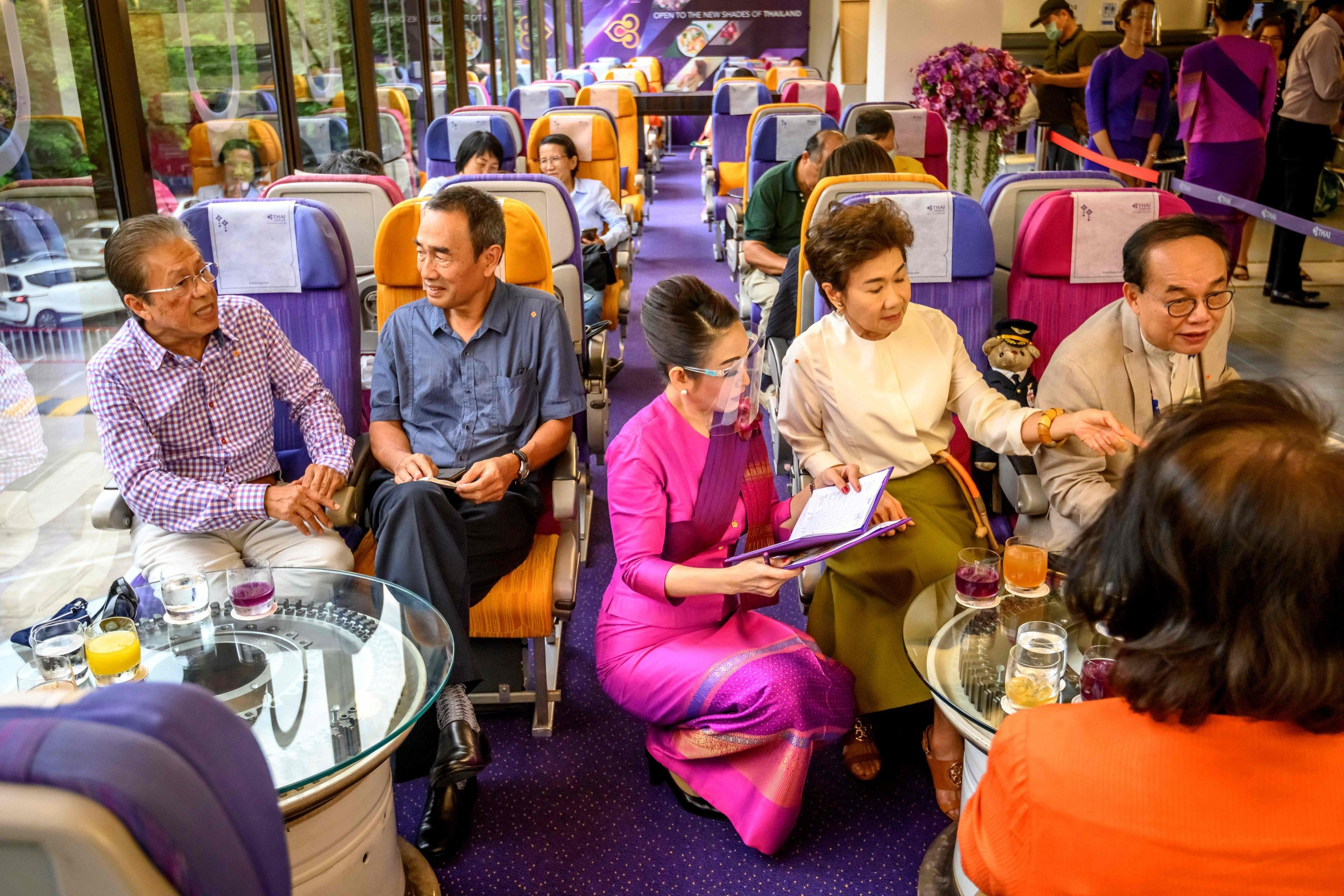 This picture taken on September 10, 2020 shows a Thai Airways flight attendant wearing a face shield as she serves customers at a pop-up air-plane-themed restaurant at the airline's headquarters in Bangkok. (AFP Photo)