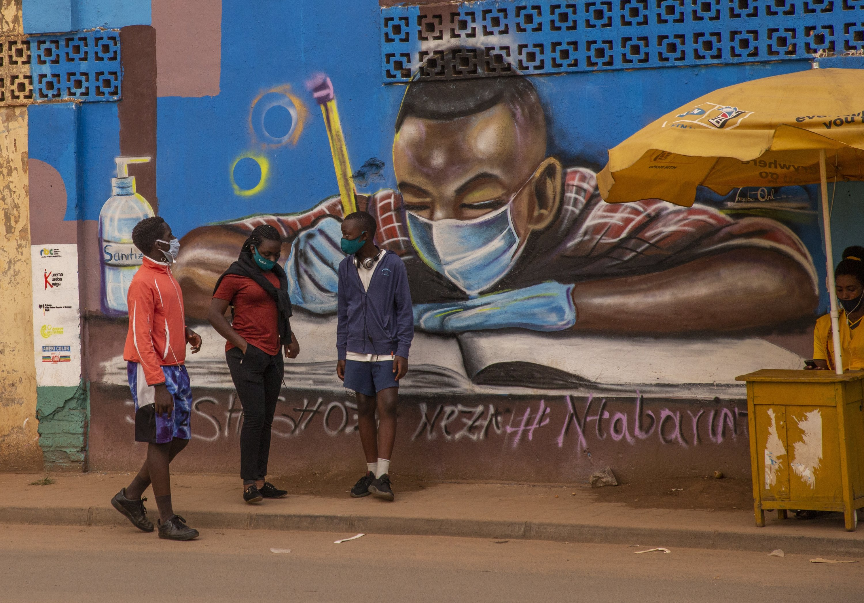 People are seen in front of another mural about the virus in Kigali, central Rwanda, Sept. 11, 2020. (AA PHOTO)
