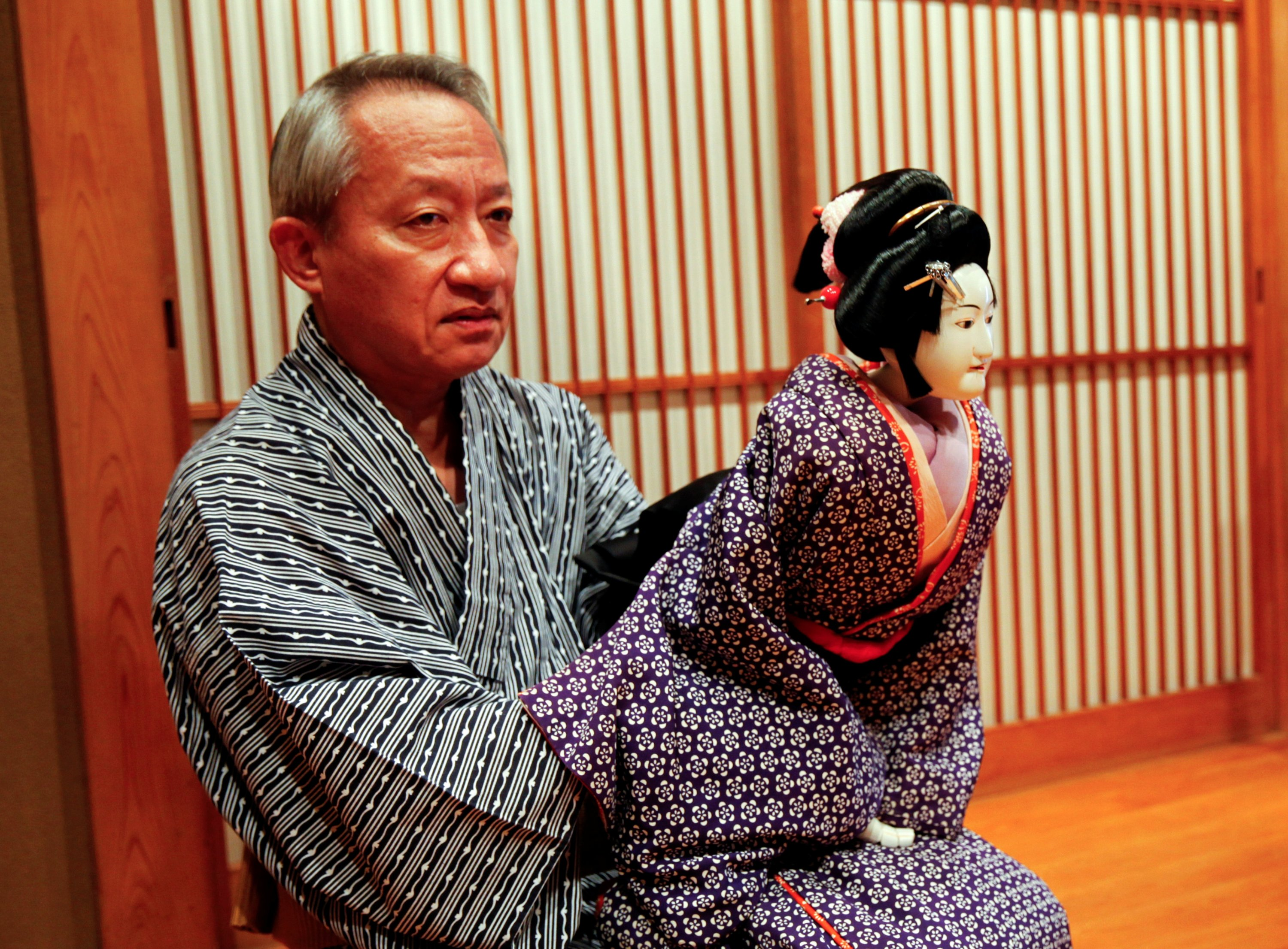 Kanjuro Kiritake poses for a photograph with a puppet in his practice room at his house in Osaka, western Japan, Aug. 28, 2020.  (REUTERS PHOTO)