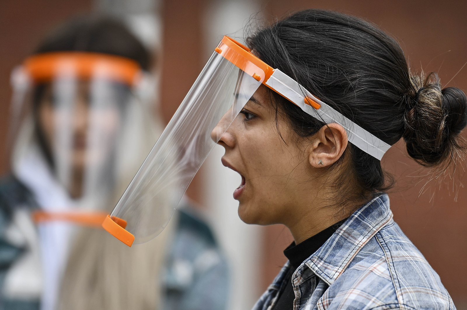 A student talks behind a face shield at a school in Cologne, Germany, May 25, 2020. (AP Photo)