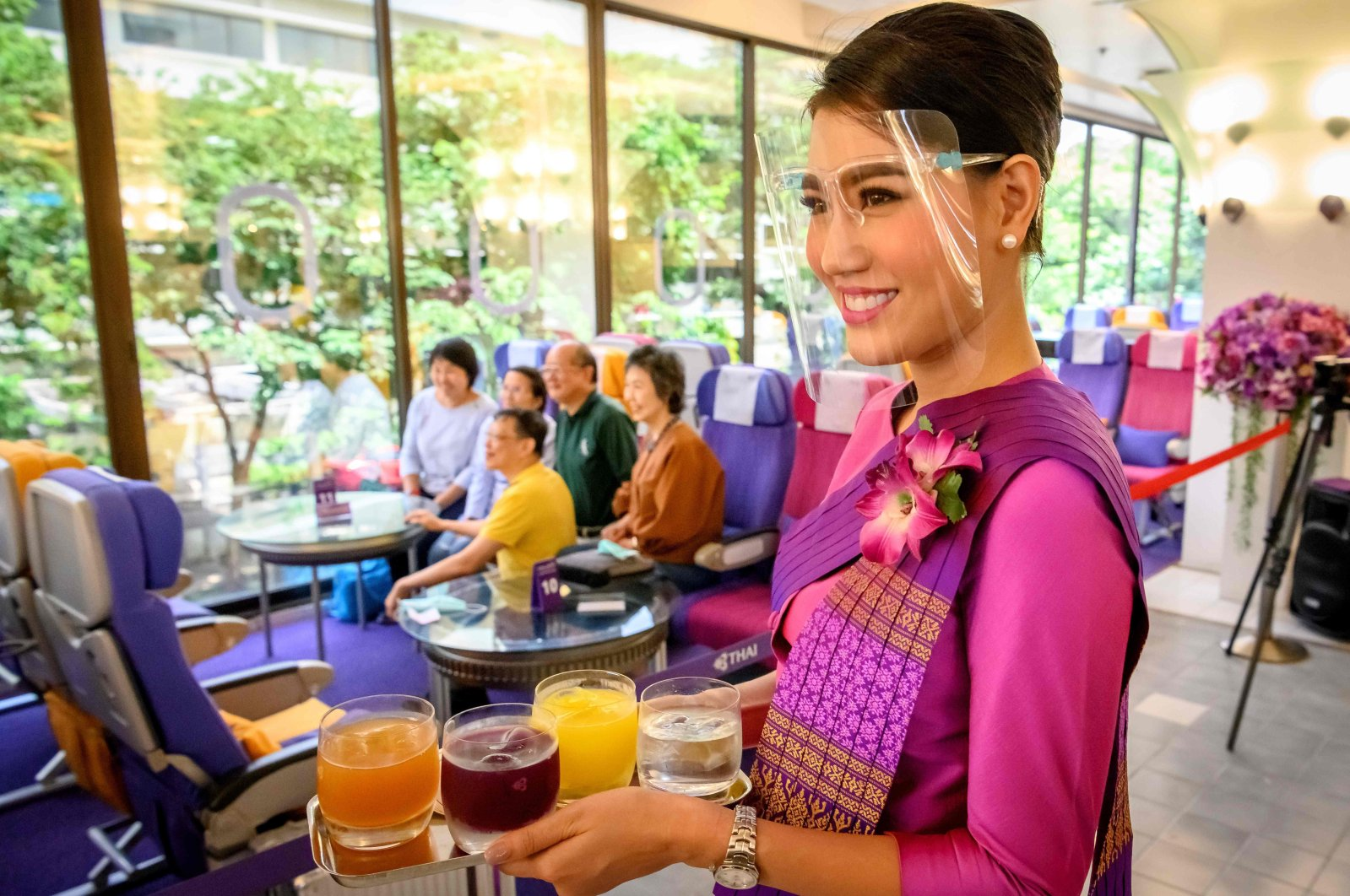 This picture taken on September 10, 2020 shows a Thai Airways flight attendant wearing a face shield as she serves drinks at a pop-up air-plane-themed restaurant at the airline's headquarters in Bangkok. (AFP Photo)