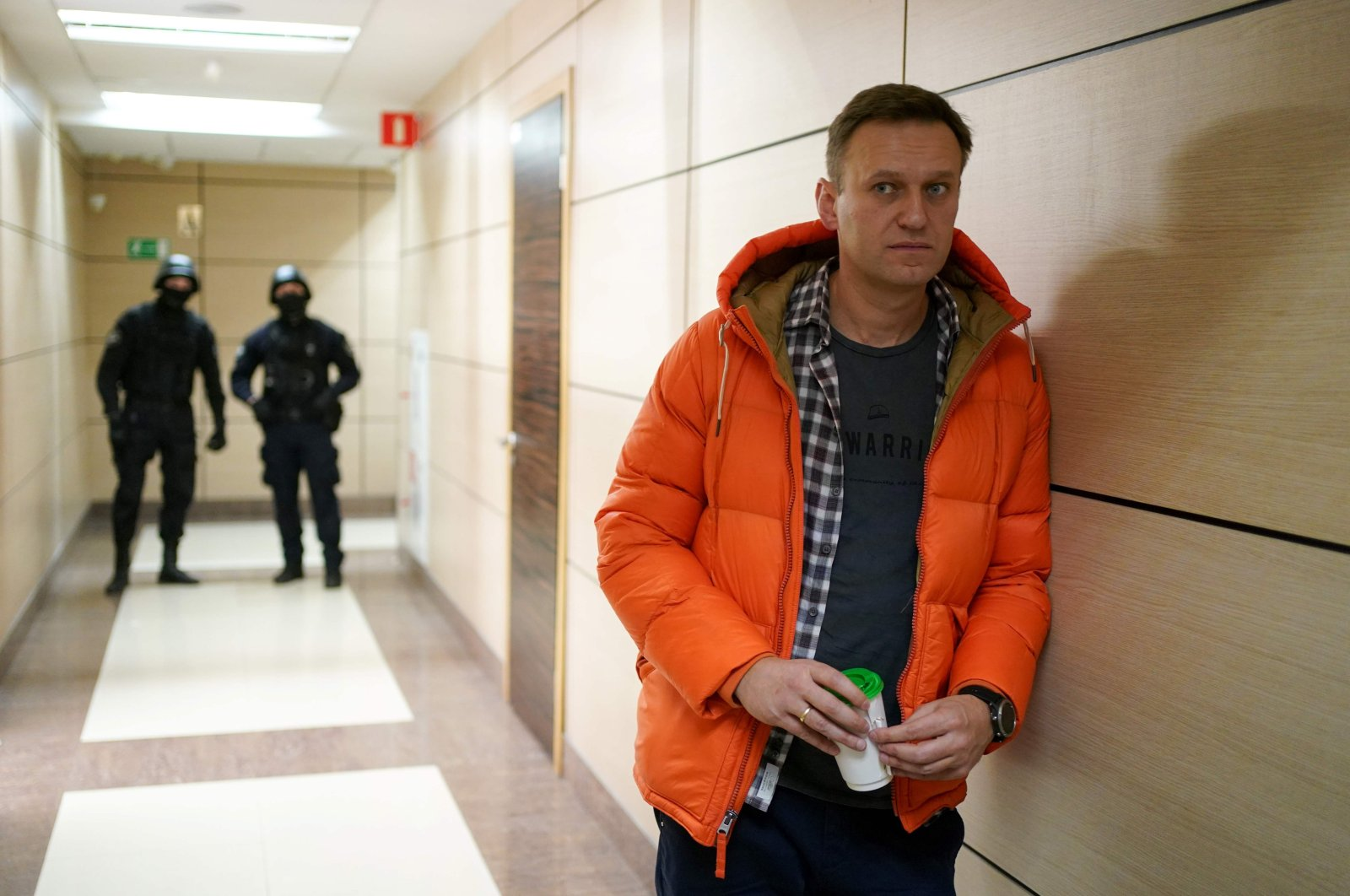 This file photo shows Russian opposition leader Alexei Navalny standing near law enforcement agents in a hallway of a business center, which houses the office of his Anti-Corruption Foundation (FBK), in Moscow, Dec. 26, 2019. (AFP Photo)
