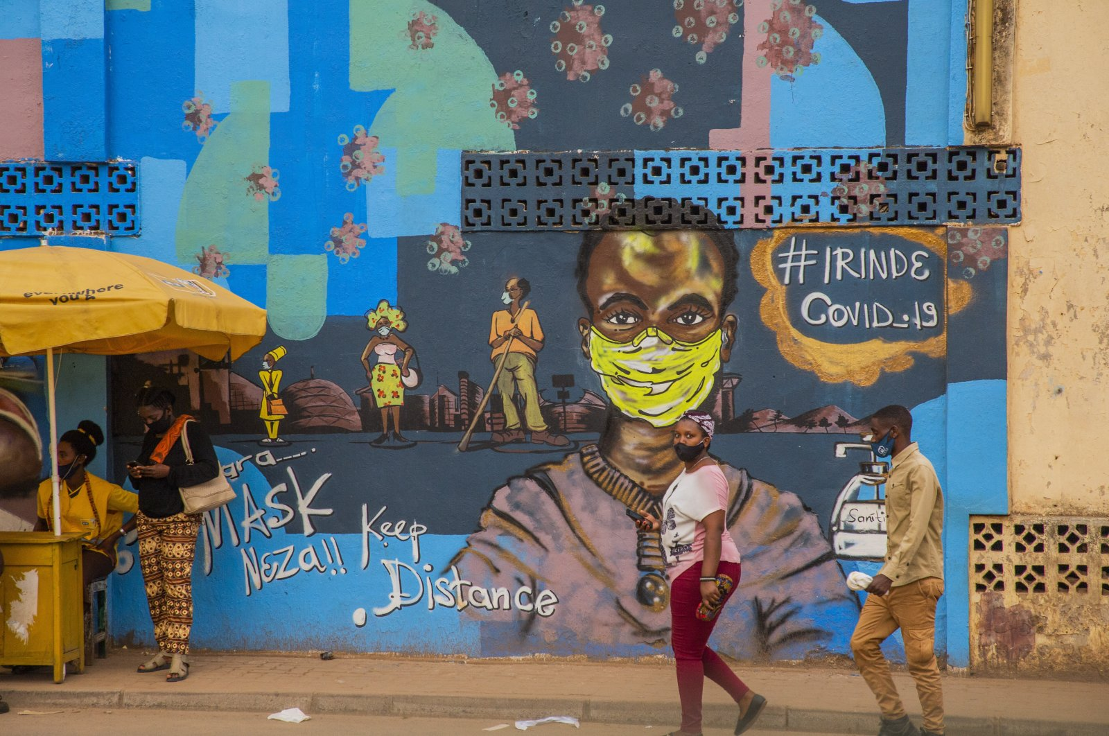 Passersby walk near a mural warning people to keep a distance and wear a mask in Kigali, central Rwanda, Sept. 11, 2020. (AA PHOTO)
