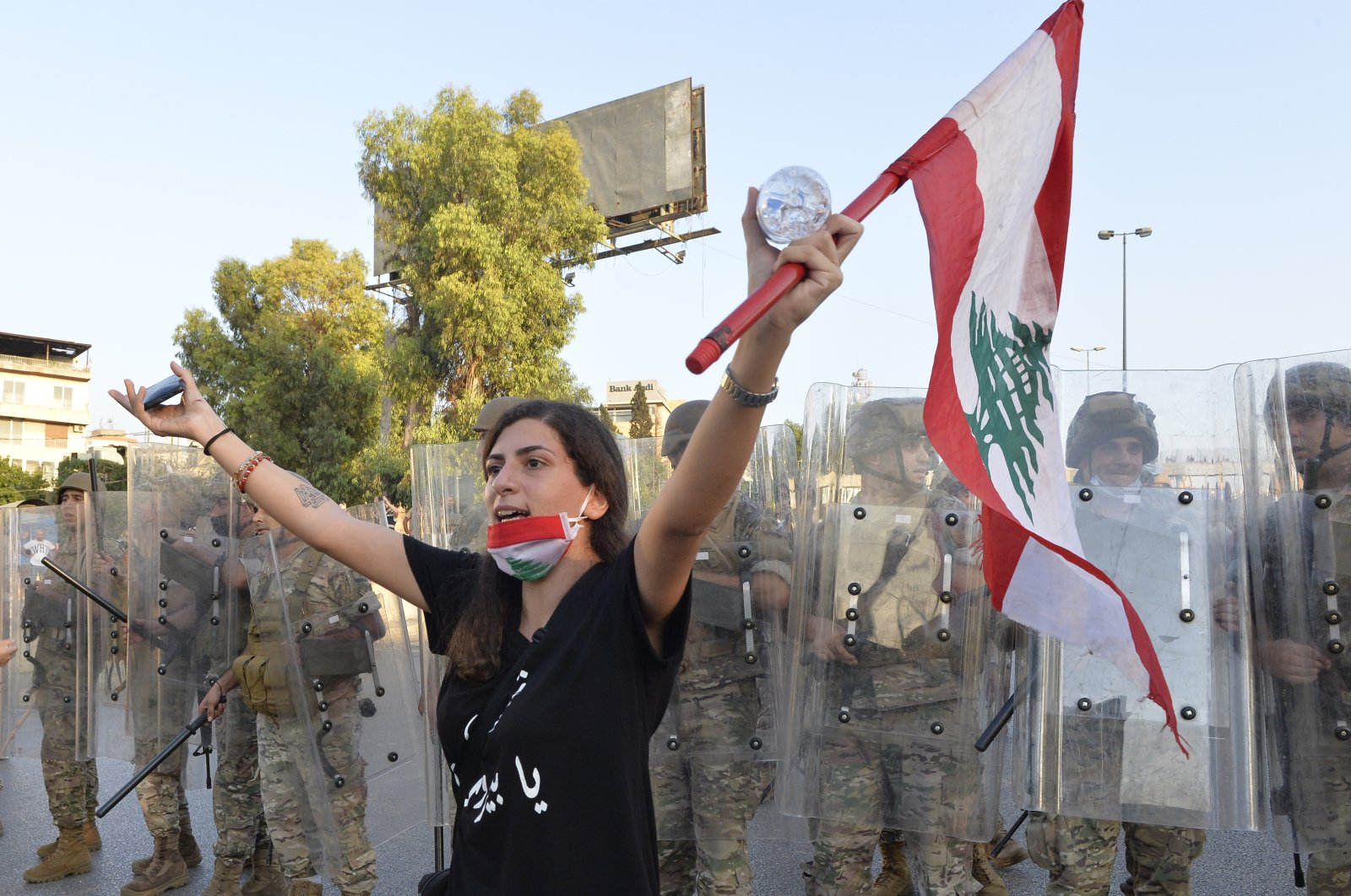 An anti-government protester carries a national flag as she shouts slogans in front of Lebanese army soldiers, Baabda, east Beirut, Sept. 12, 2020. (EPA Photo)