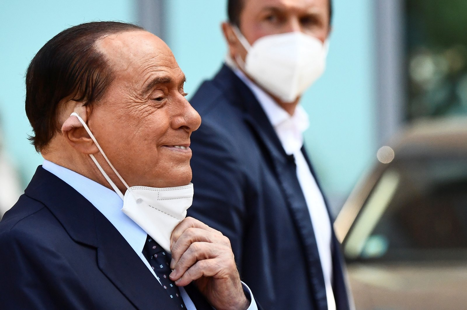 Former Italian Prime Minister Silvio Berlusconi adjusts his protective mask as he leaves Milan's San Raffaele hospital, where he was being treated after testing positive for the coronavirus and diagnosed with mild pneumonia, in Milan, Italy, Sept. 14, 2020. (Reuters Photo)